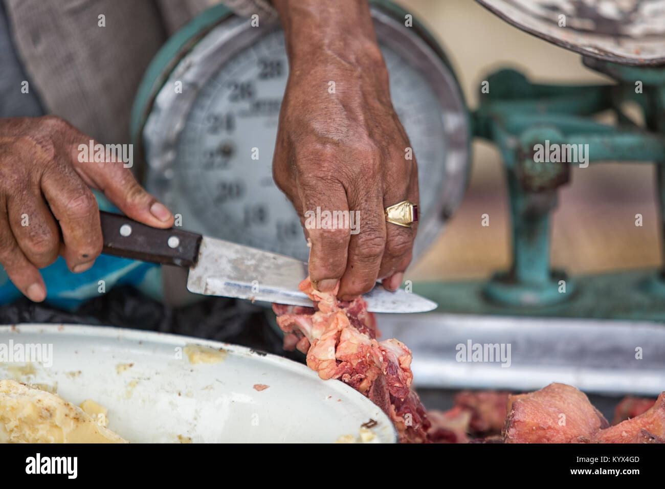 Otavalo, Ecuador - December 30, 2017: closeup of butcher's hand cutting meat with knife in the weekly farmers - Stock Image