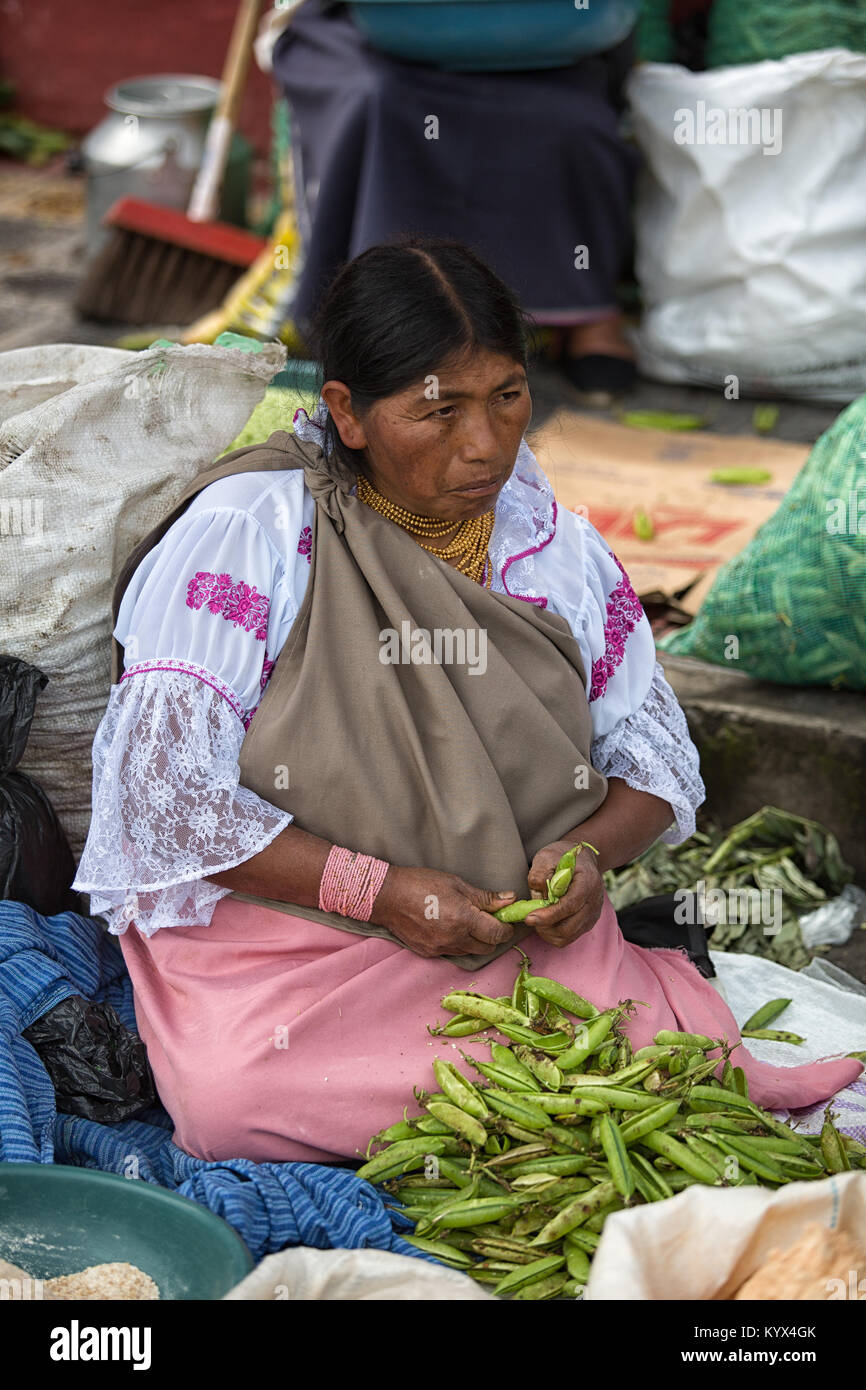 Otavalo, Ecuador - December 30, 2017: closeup of an indigenous woman cleaning peas in the weekly farmers market - Stock Image