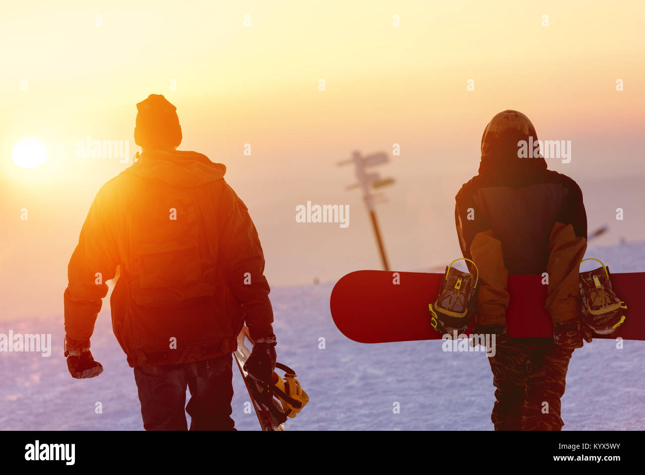 Two snowboarders walking against sunset sky - Stock Image