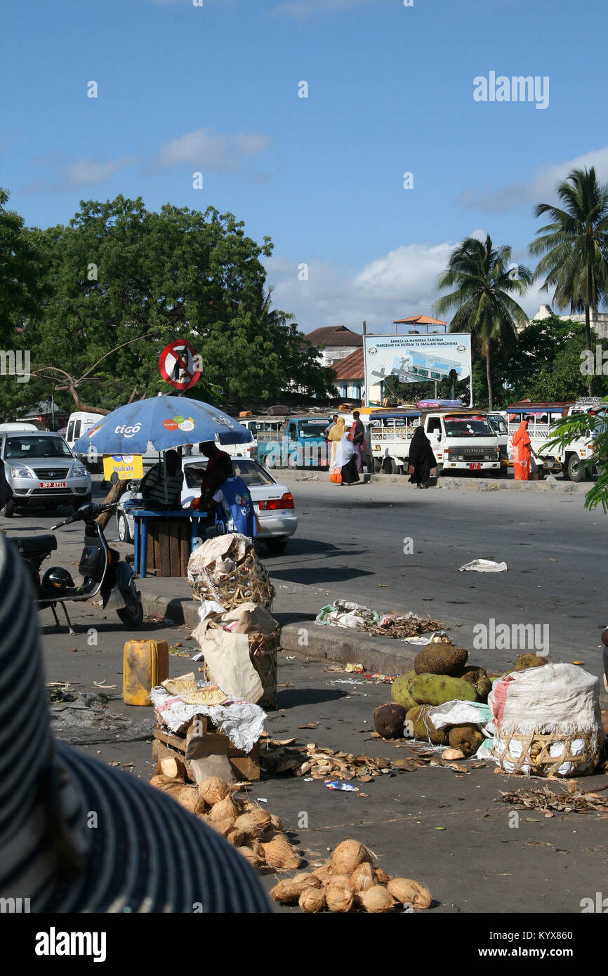 Rubbish on the sidewalk of a street packed with cars, Stone Town, Zanzibar, Tanzania. - Stock Image