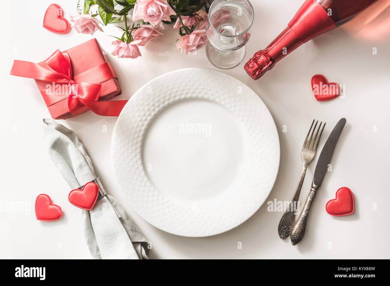 Valentines day dinner with table place setting with red gift glass for ch&agne a bottle of ch&agne pink roses hearts with silverware on white & Valentines day dinner with table place setting with red gift glass ...