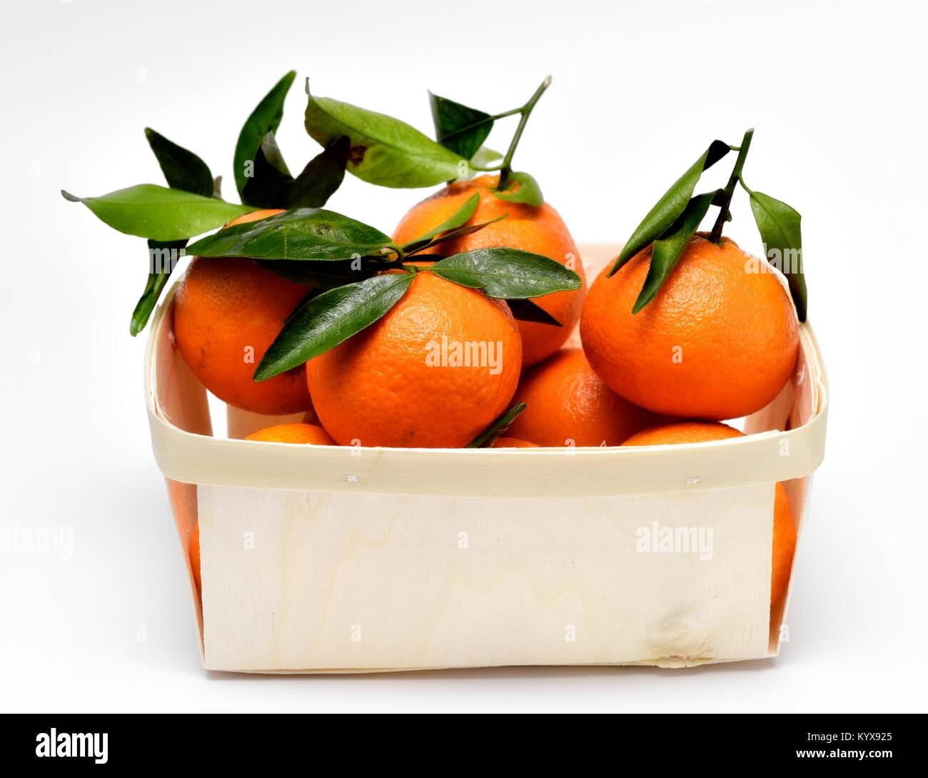 Oranges with green leaves sold in a small crate - Stock Image
