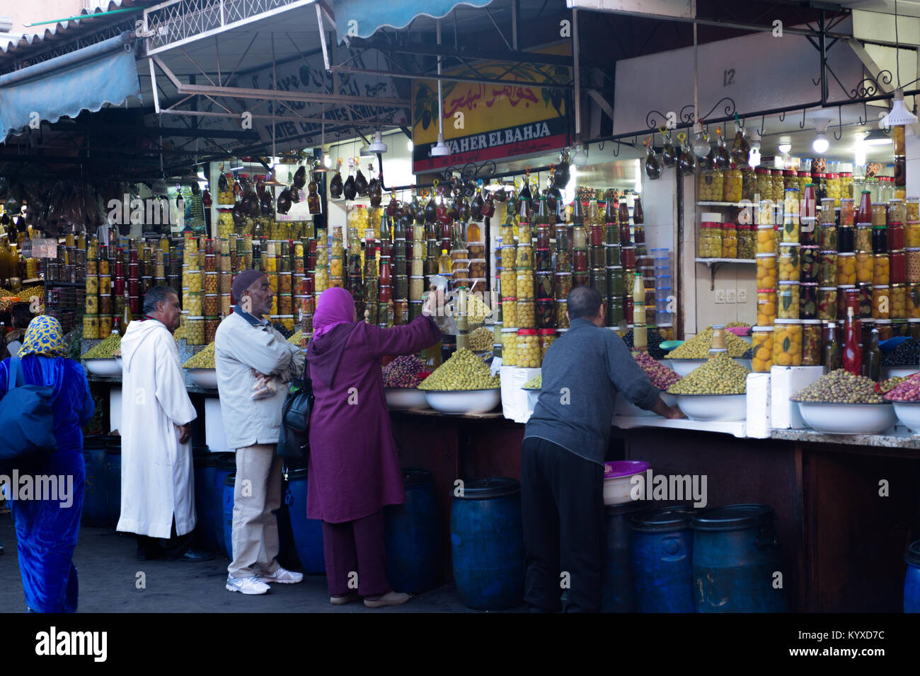 Local people buying jars of pickles at the spices stands in Jemma el-Fnaa, Medina, Marrakesh, Morocco Stock Photo