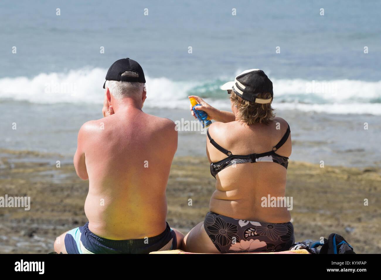 Brirs abroad: woman applying spray suncream to sunburnt back of man on beach in Spain. - Stock Image