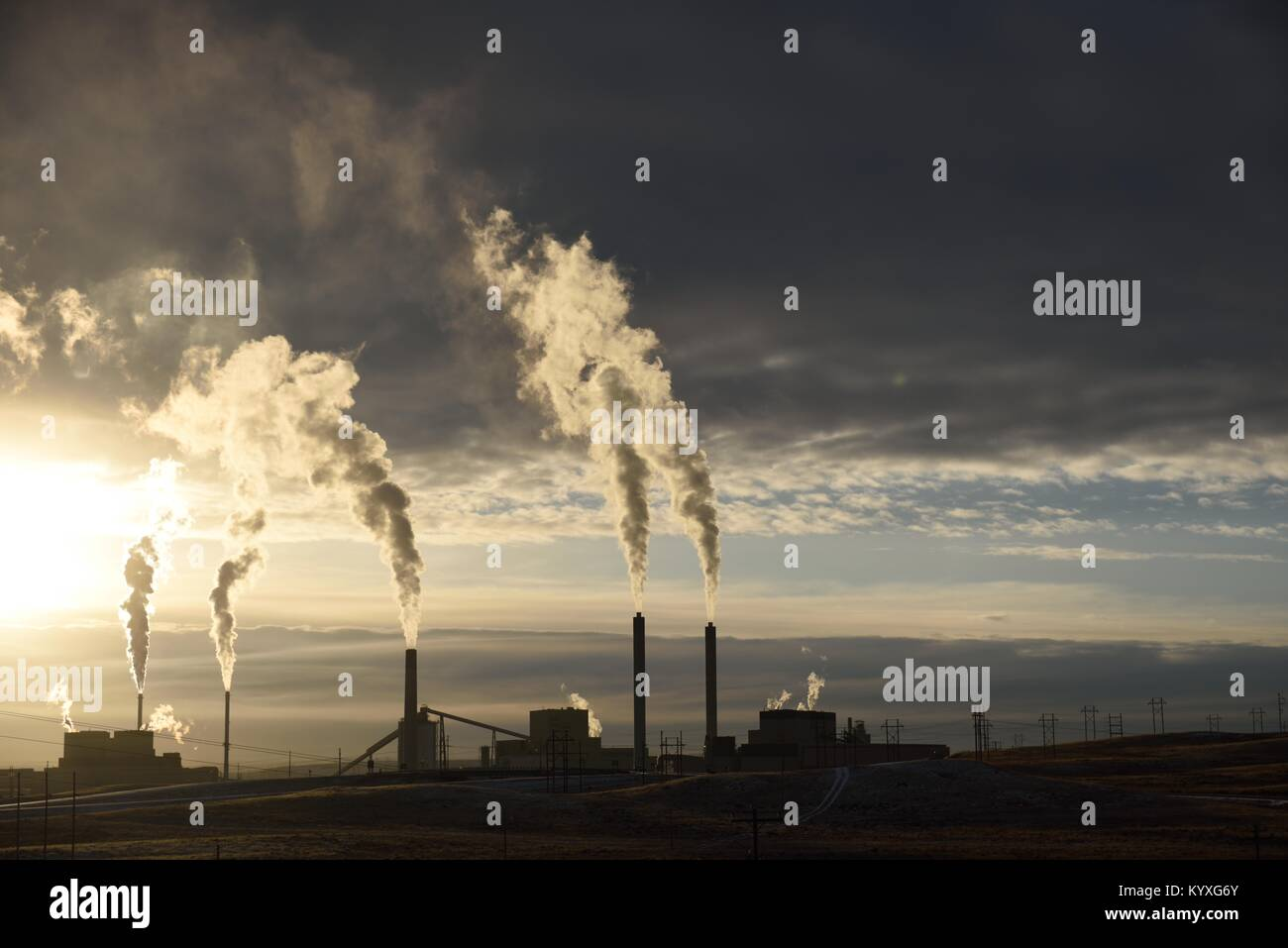 Emissions rising from the smoke stacks of an industrial coal-fired power plant at sunset near Gillette, Wyoming - Stock Image