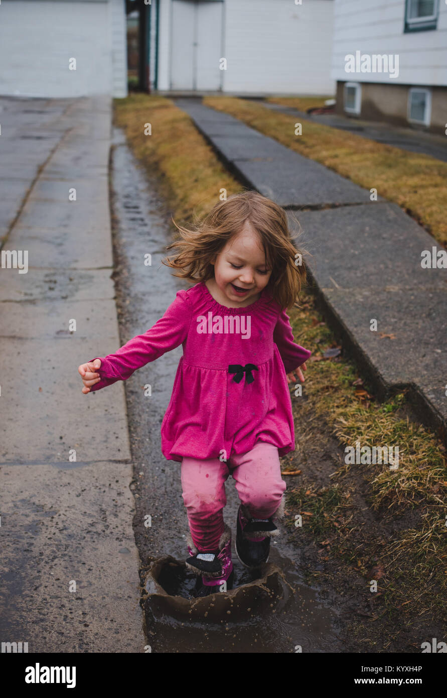 Toddler girl wearing pink, jumping in a mud puddle in a driveway on a rainy day. - Stock Image