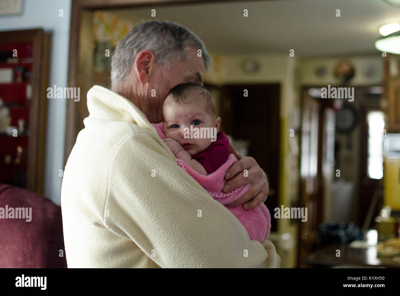 A grandfather holds his two month old granddaughter in a pink blanket. - Stock Image