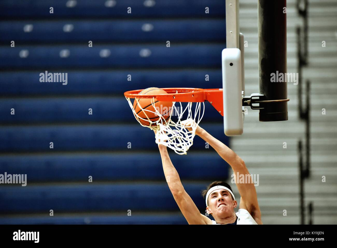 Forward hanging at the rim while slamming home two points during a high school game. USA. - Stock Image