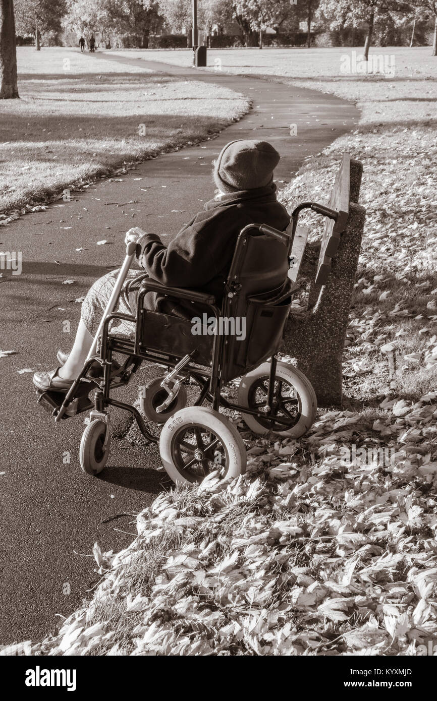90 year old woman in wheelchair in public park. UK: care, loneliness, mobility, ageing population..., concept image. - Stock Image