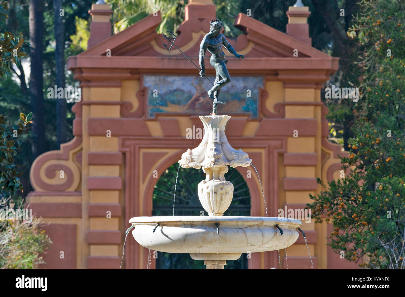 ALCAZAR SEVILLE SPAIN THE FORMAL GARDENS A STATUE OF NEPTUNE ON A FOUNTAIN IN THE GARDEN WITH ARCHWAY AND ORANGE - Stock Image