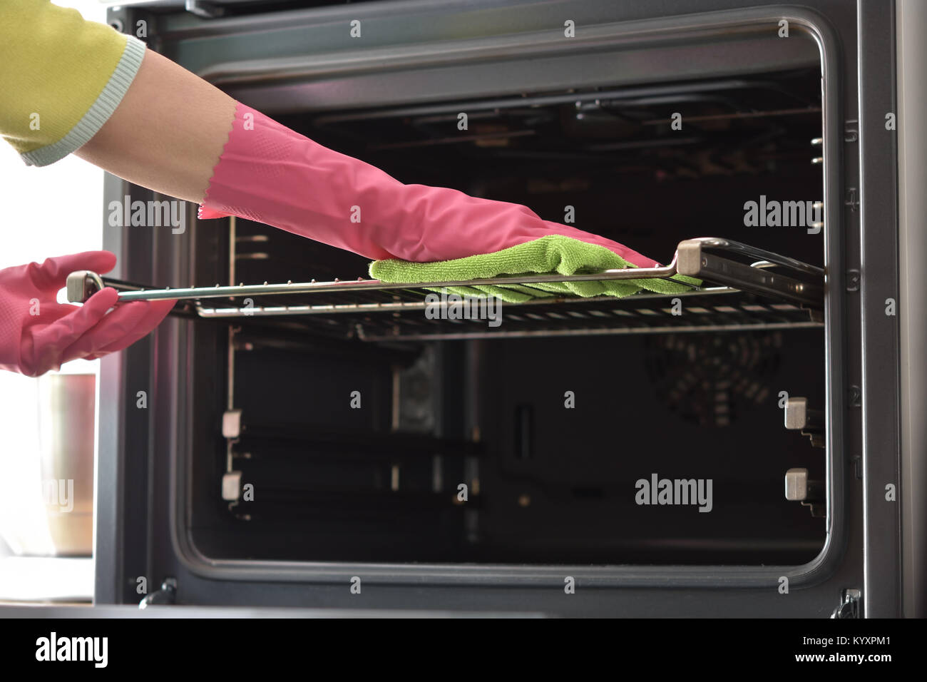 Cleaning the oven. Woman's hand in household cleaning gloves cleans oven inside. Clean oven in kitchen. - Stock Image