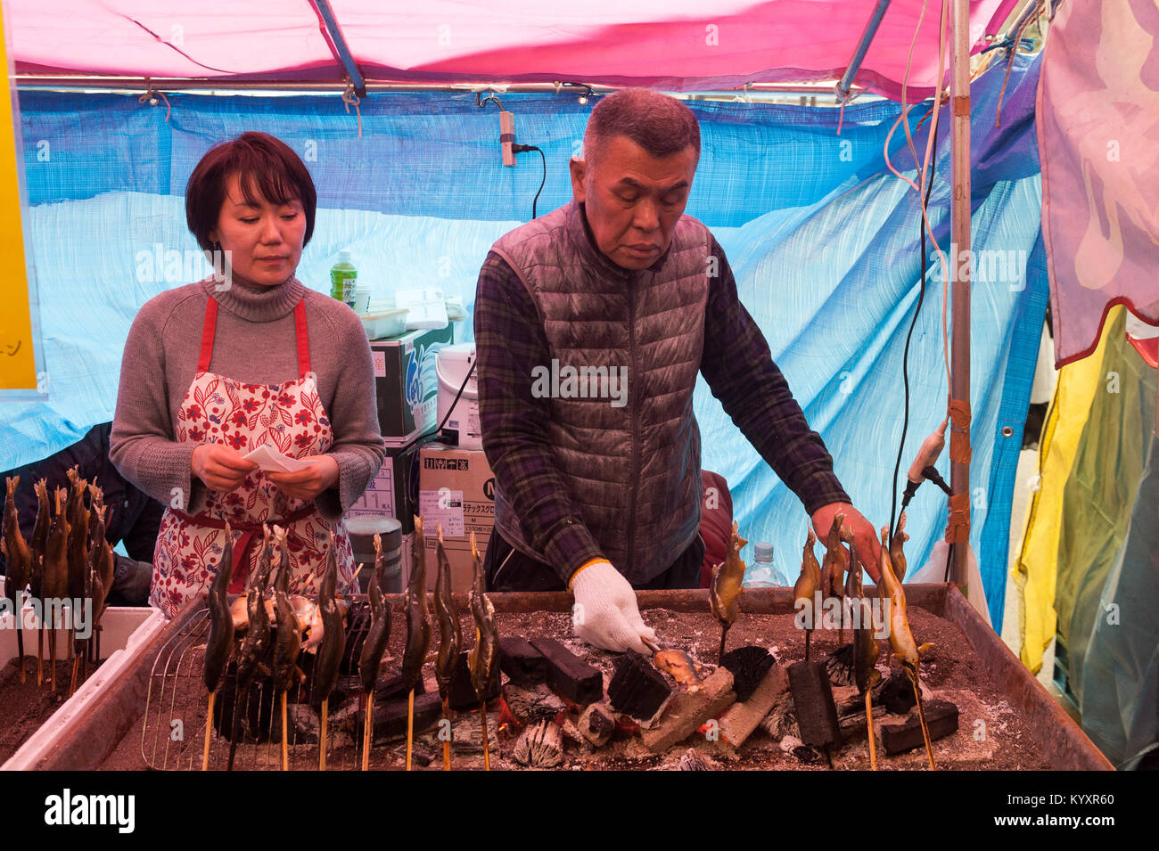 31.12.2017, Tokyo, Japan, Asia - A man prepares freshly roasted fish skewers at a street stall in Tokyo's city district Stock Photo