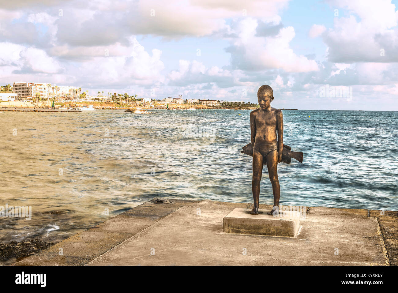 Statue of a boy with a fish on the shore of the Mediterranean Sea. - Stock Image