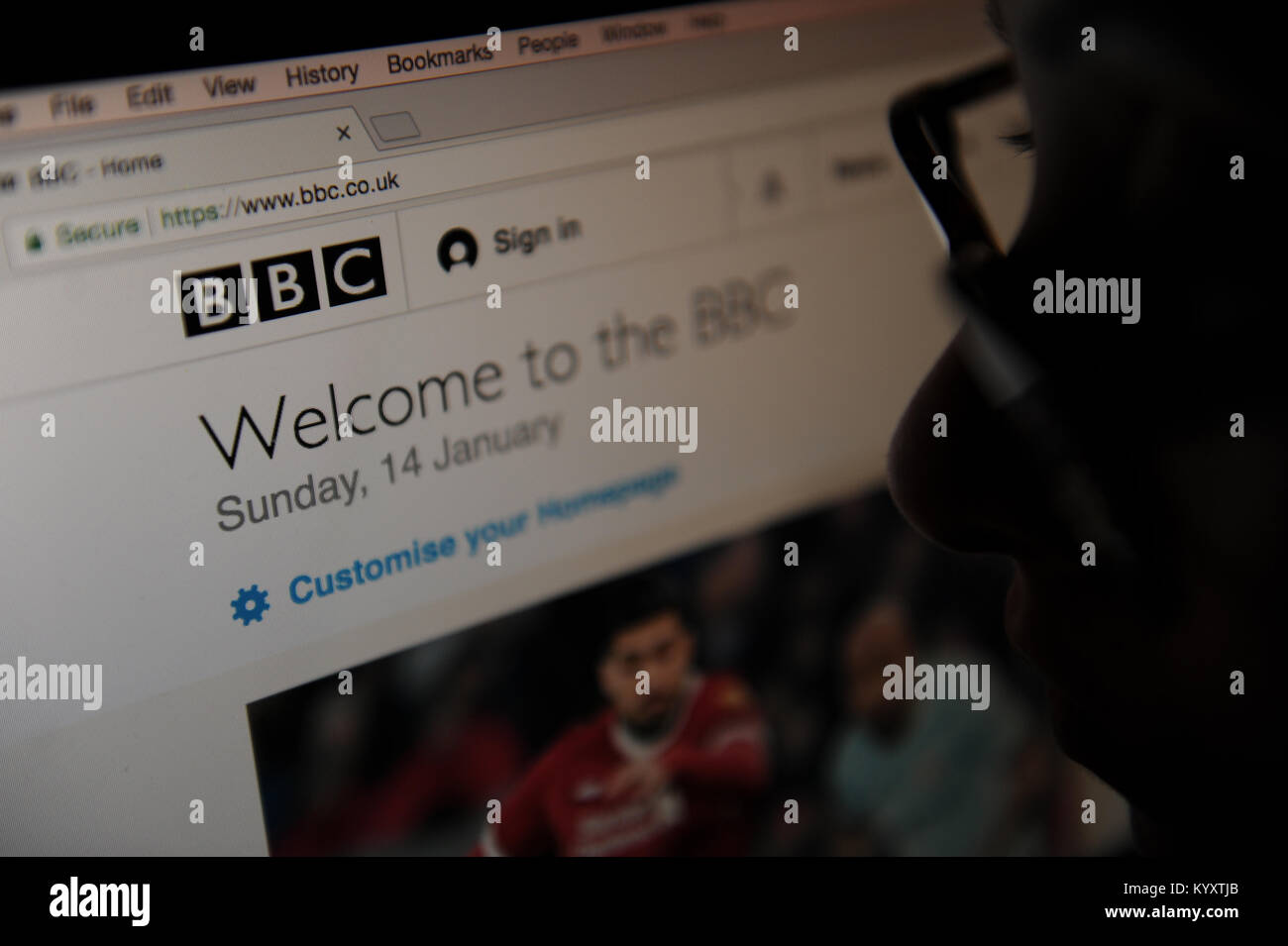 A woman looks at the BBC news homepage - Stock Image