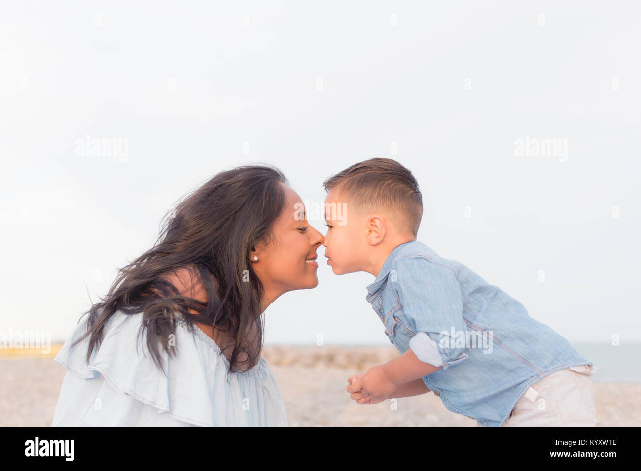Mother rubbing noses with son against clear sky - Stock Image