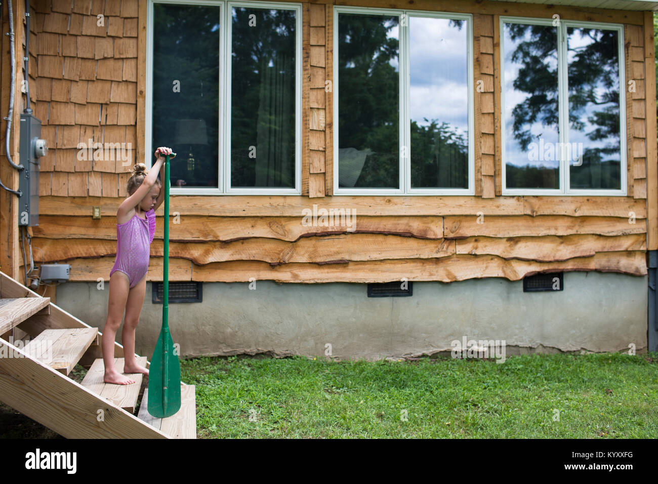 Girl wearing one piece swimsuit while holding oar on steps - Stock Image