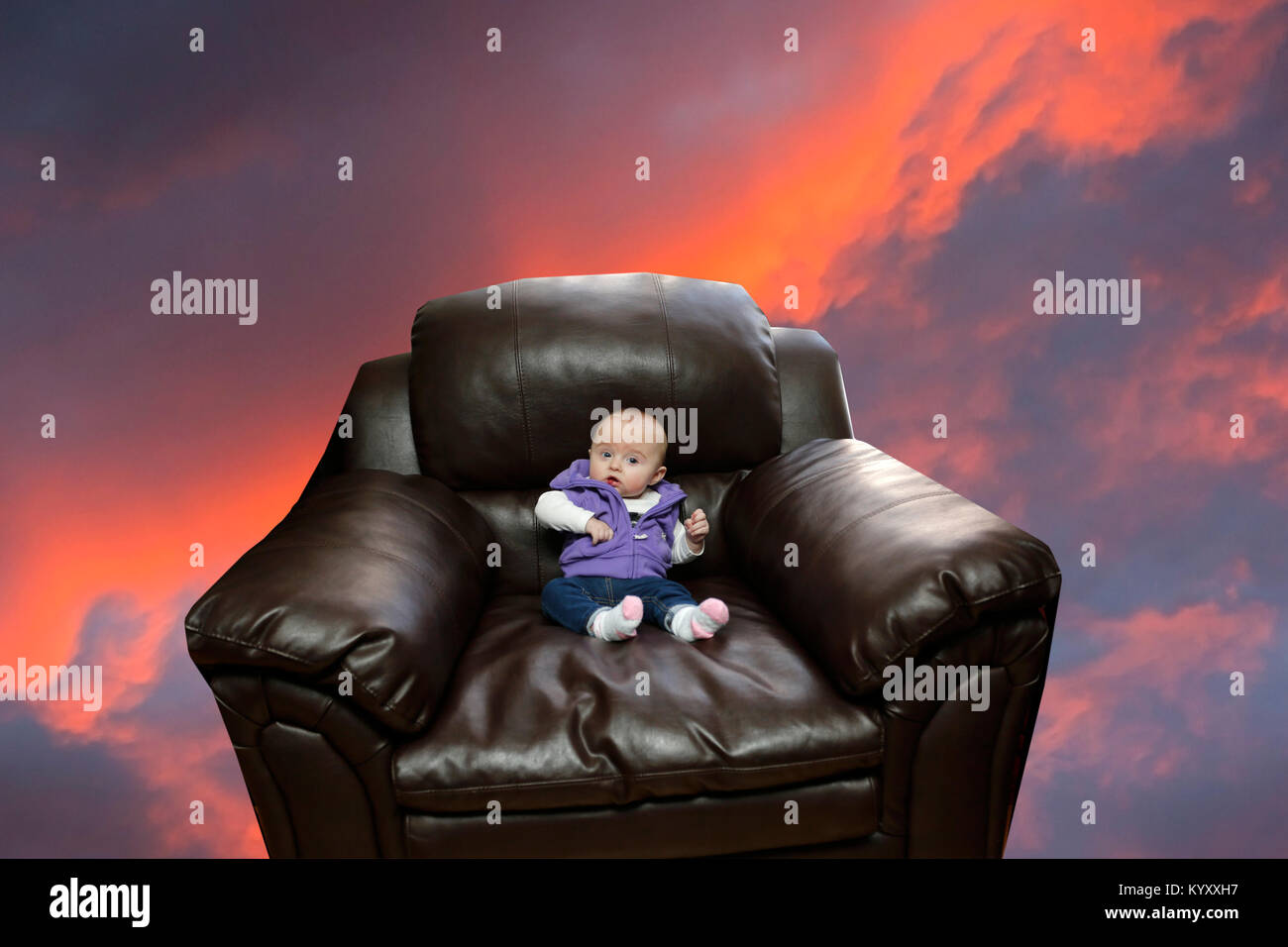 girl child sitting in oversize armchair looking concerned - Stock Image