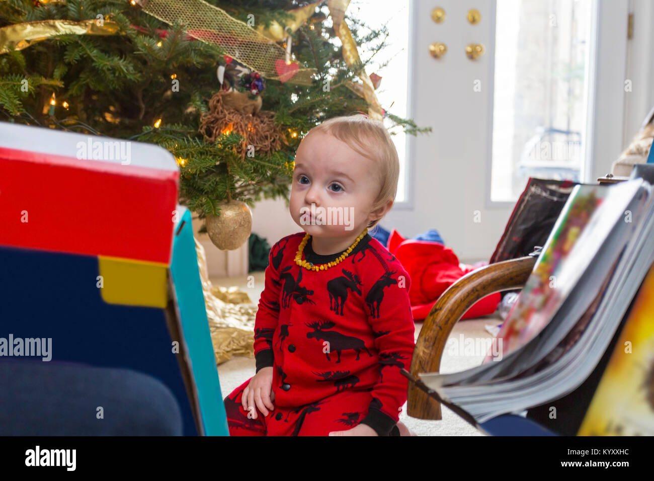 sad 1 year old child in red pyjamas sitting on floor looking up beside Christmas tree - Stock Image