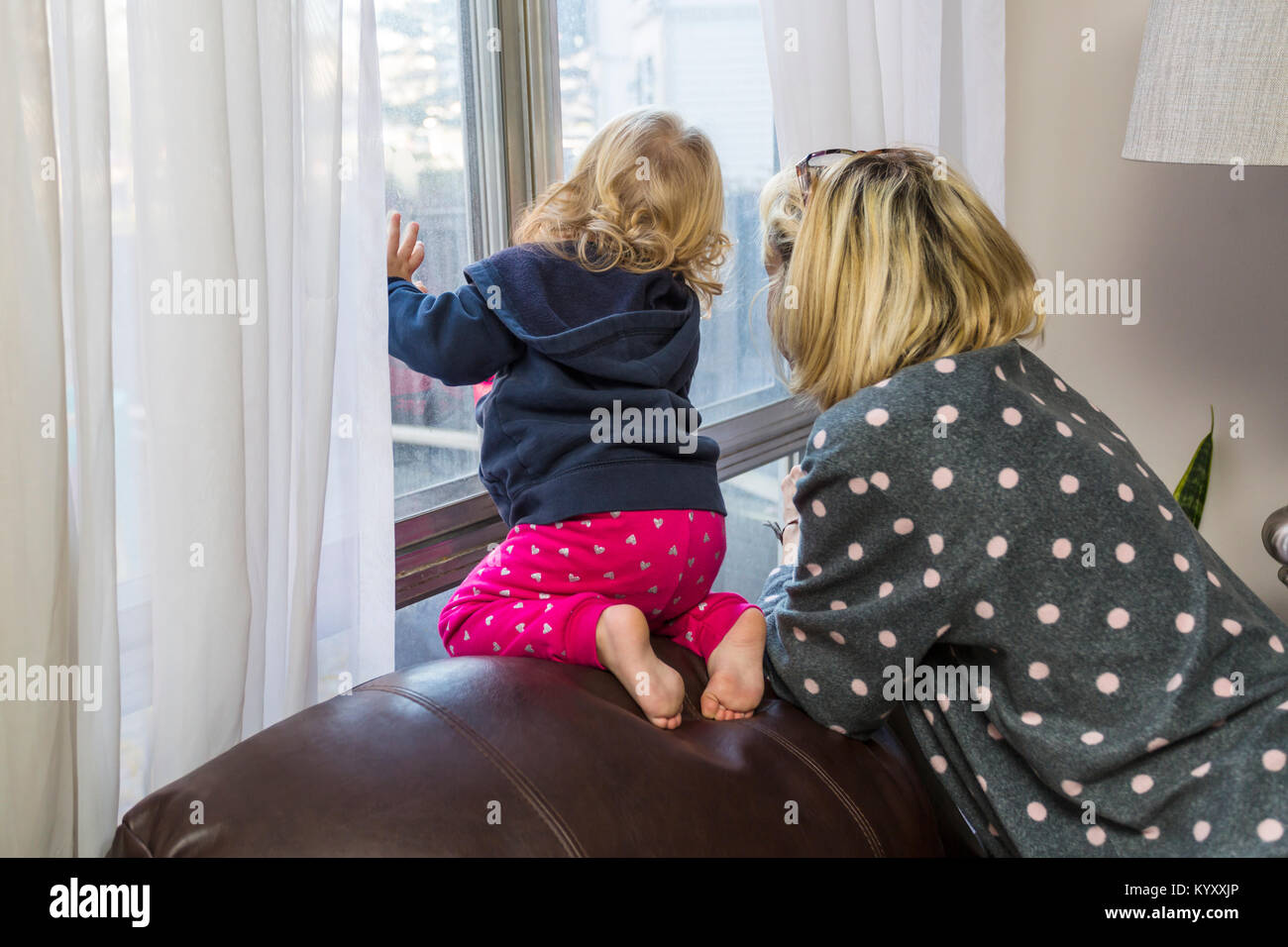 mother and child looking out window child is at risk of falling - Stock Image