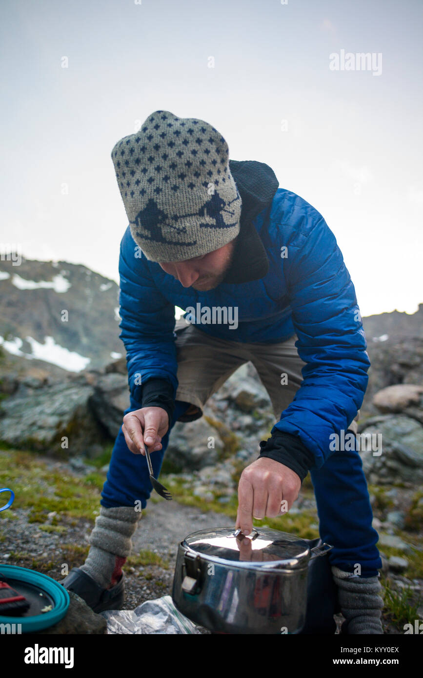 Hiker adjusting cooking utensil while preparing food at Olympic National Park - Stock Image