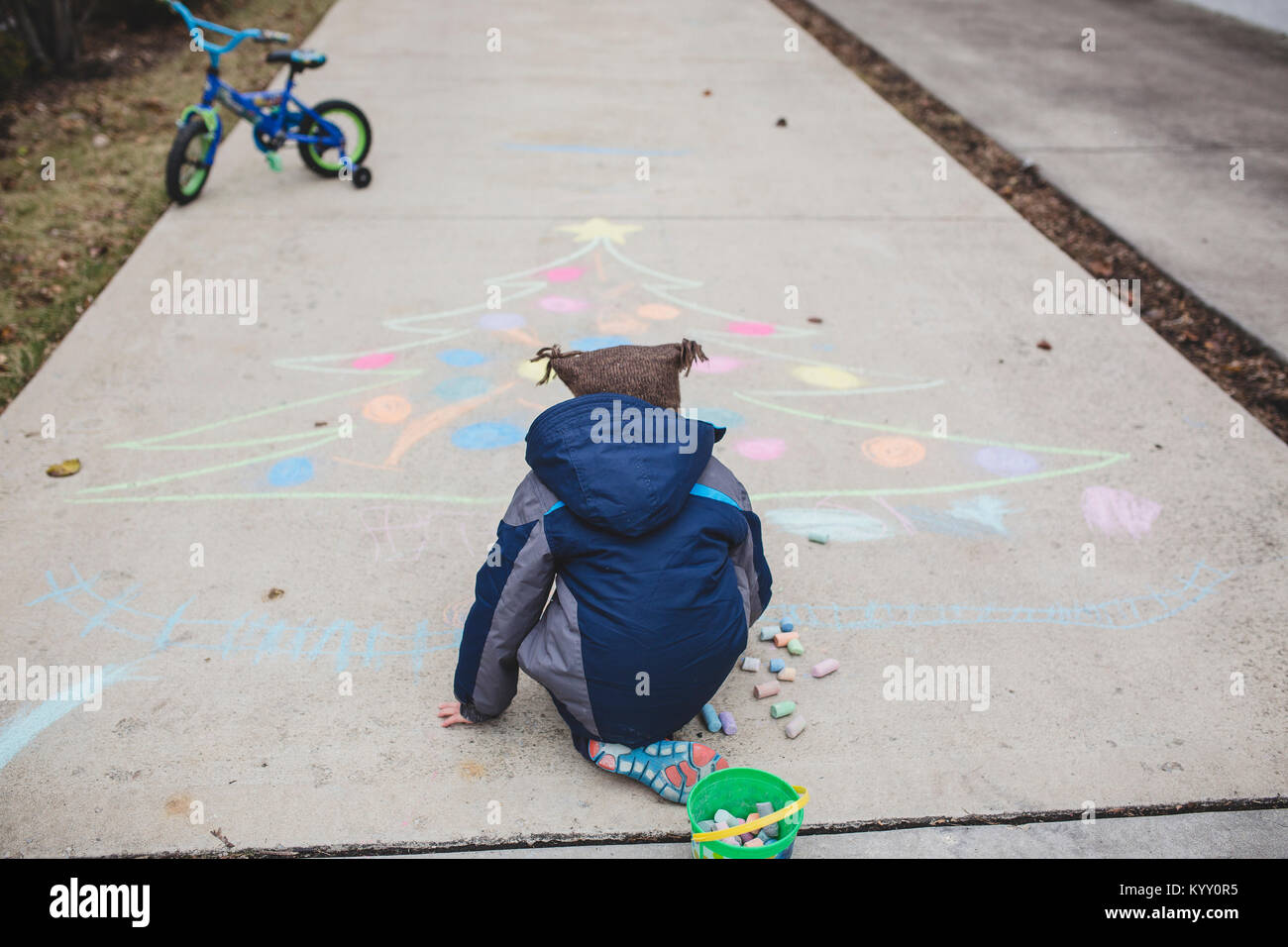 Rear view of boy in warm clothing drawing Christmas tree with chalks on footpath - Stock Image