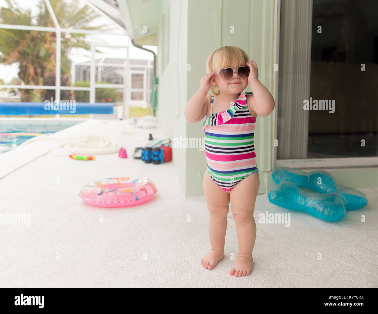 Girl in swimwear wearing heart shape sunglasses while standing at poolside - Stock Image