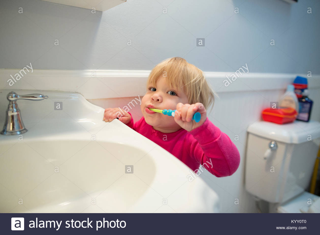 Portrait of girl brushing teeth by bathroom sink at home - Stock Image