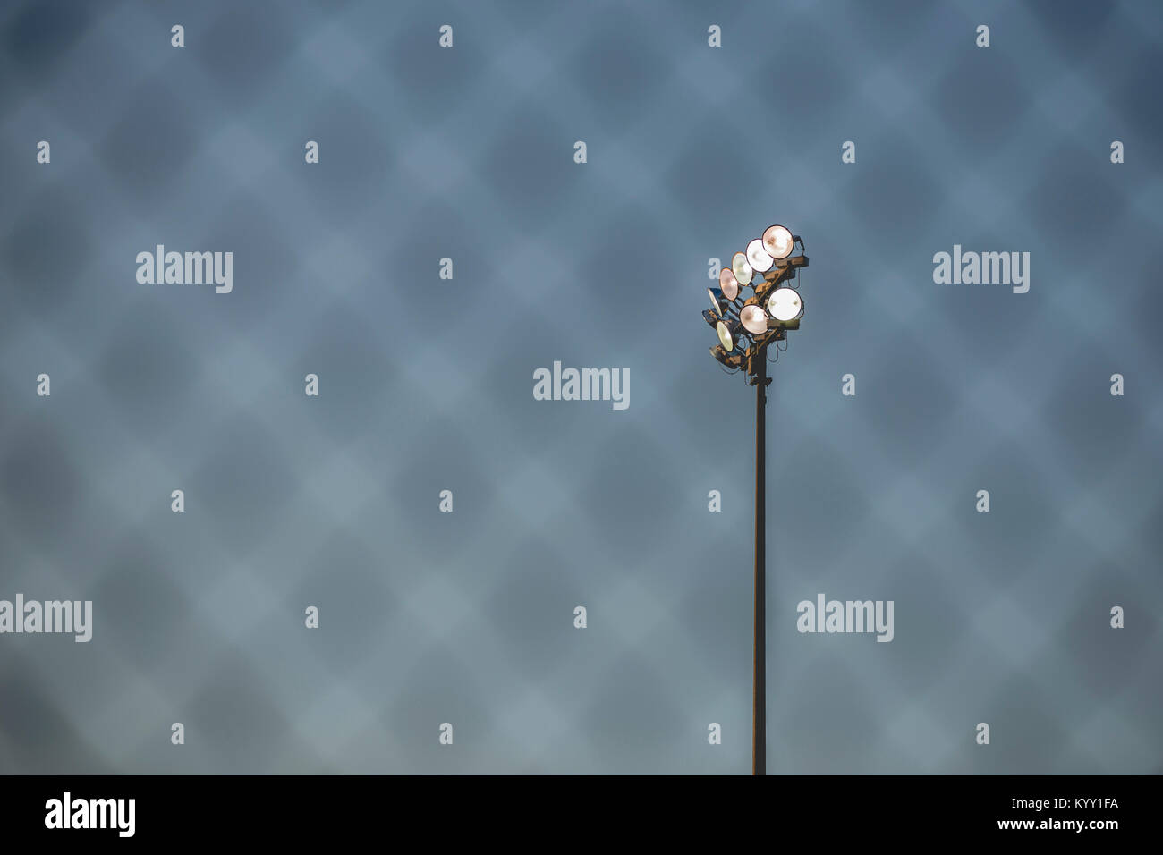 Low angle view of floodlight against sky seen through fence at baseball stadium - Stock Image
