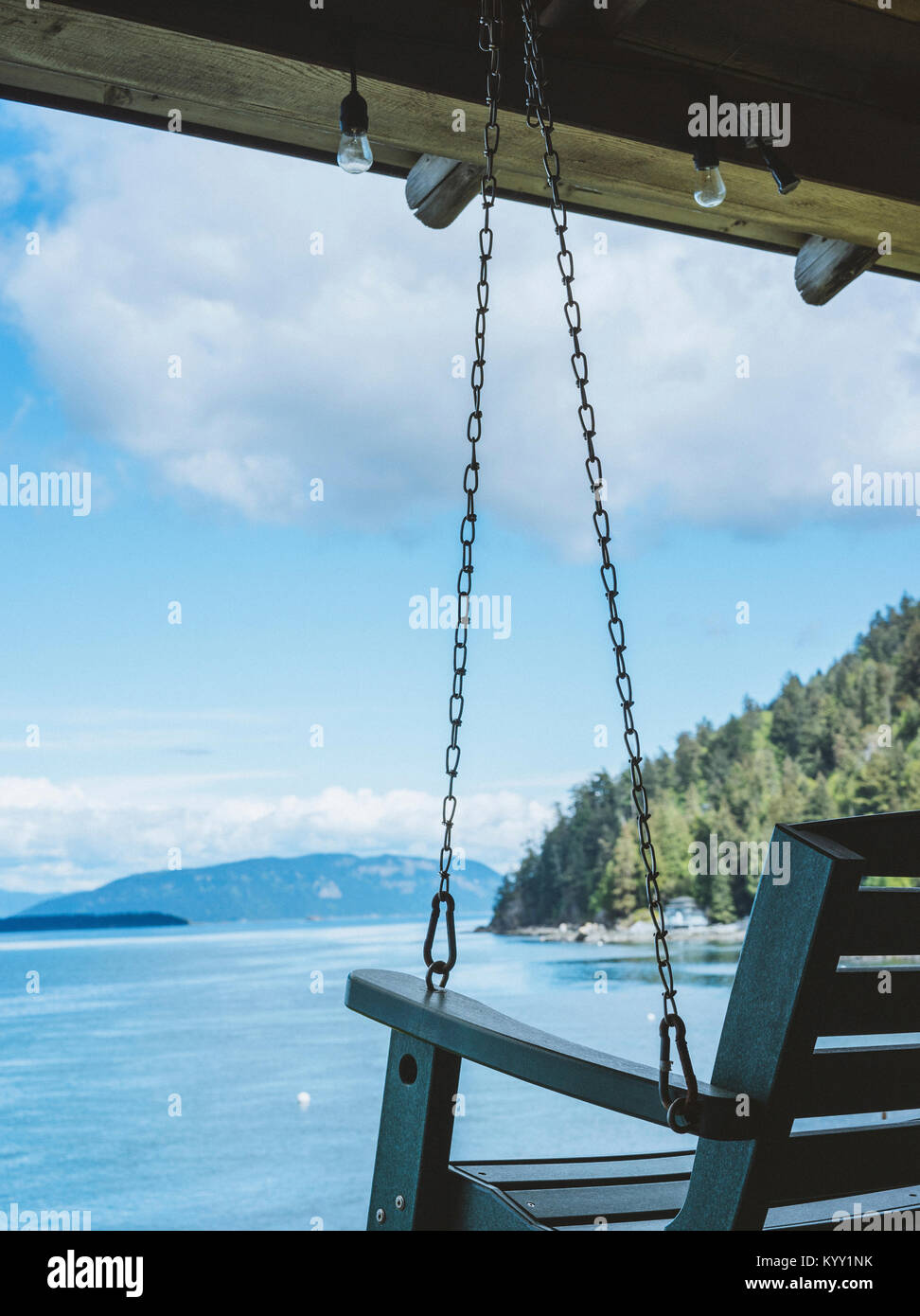 Porch swing against sea - Stock Image