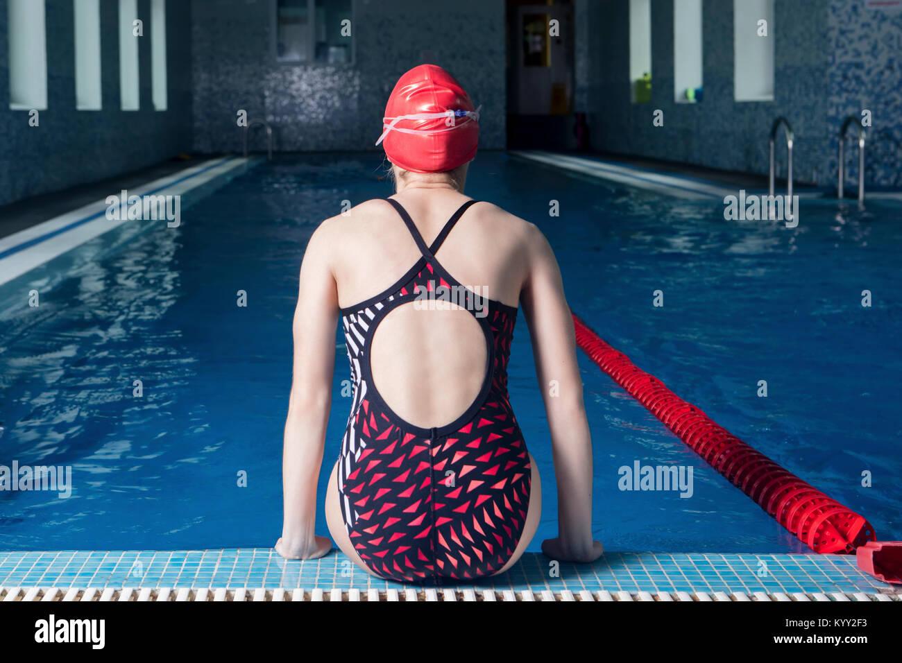 Rear view of teenage girl wearing swimwear while sitting at poolside - Stock Image