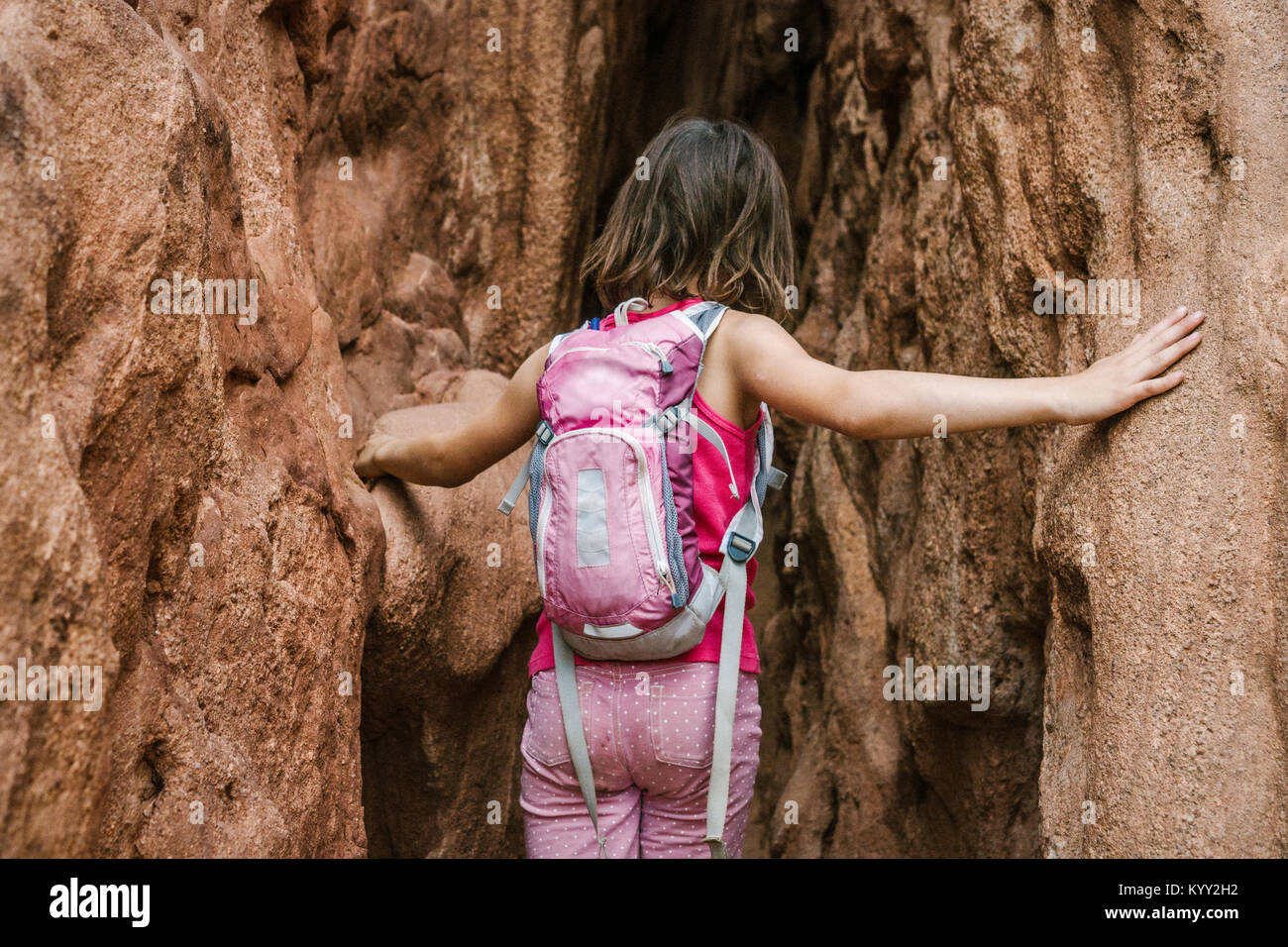 Rear view of girl with backpack exploring amidst rock formations - Stock Image