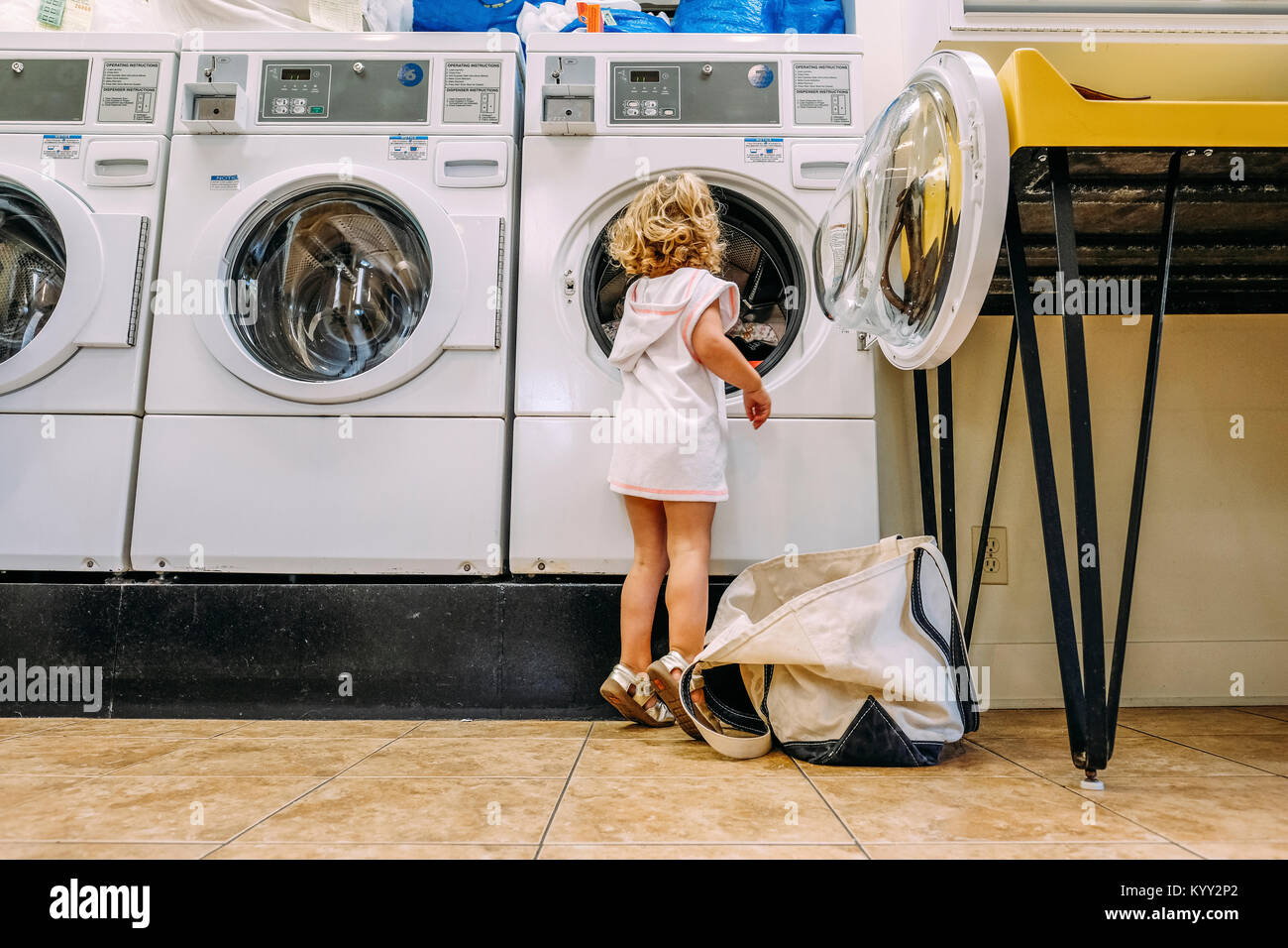 Rear view of girl putting clothing in washing machine at Laundromat - Stock Image