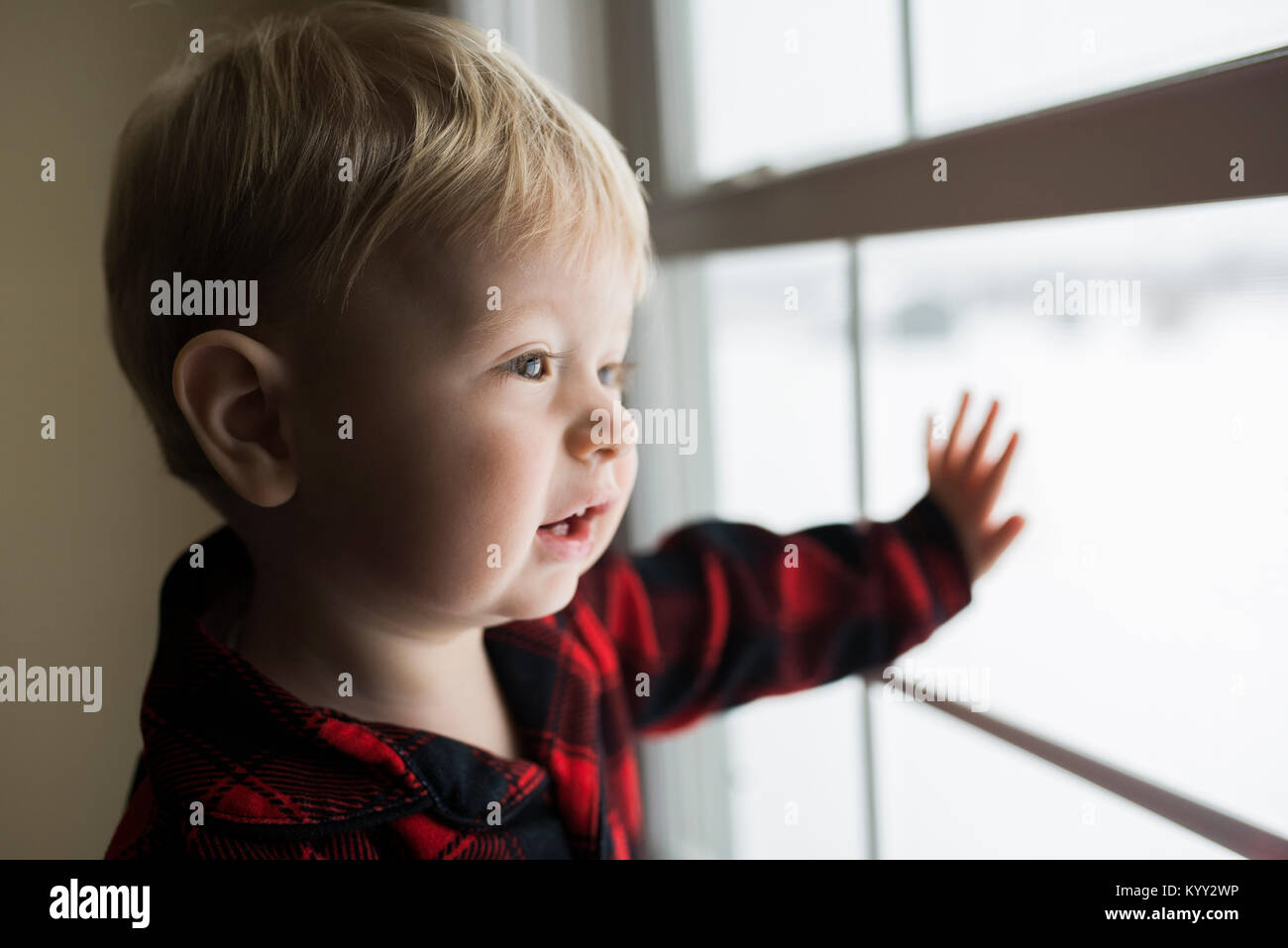 Cute boy looking through window at home - Stock Image