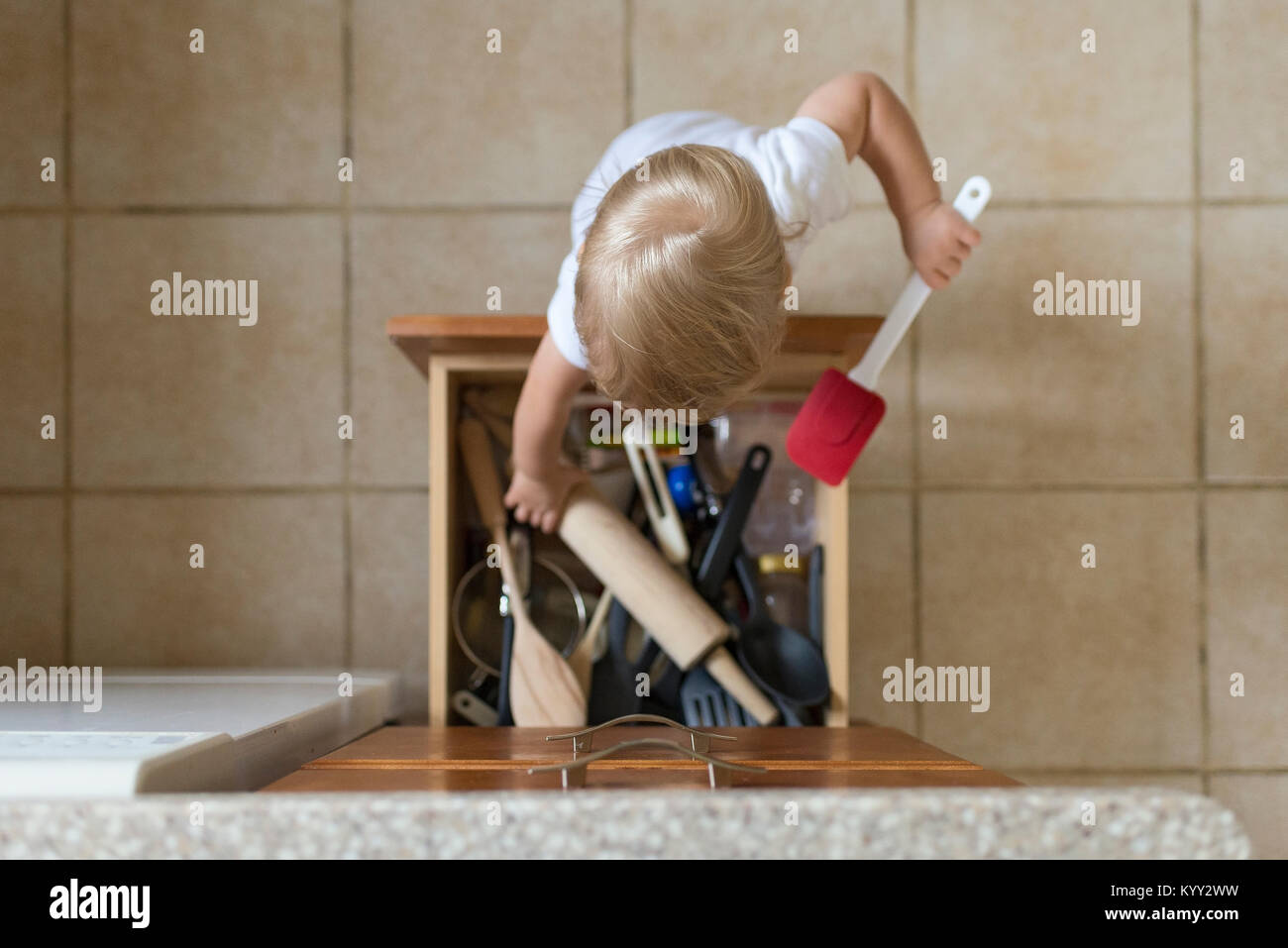 Overhead view of baby boy removing kitchen utensils from drawer - Stock Image
