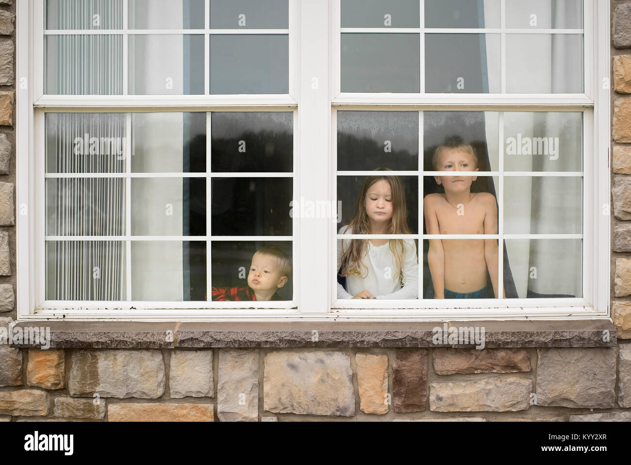 Siblings looking through window at home - Stock Image