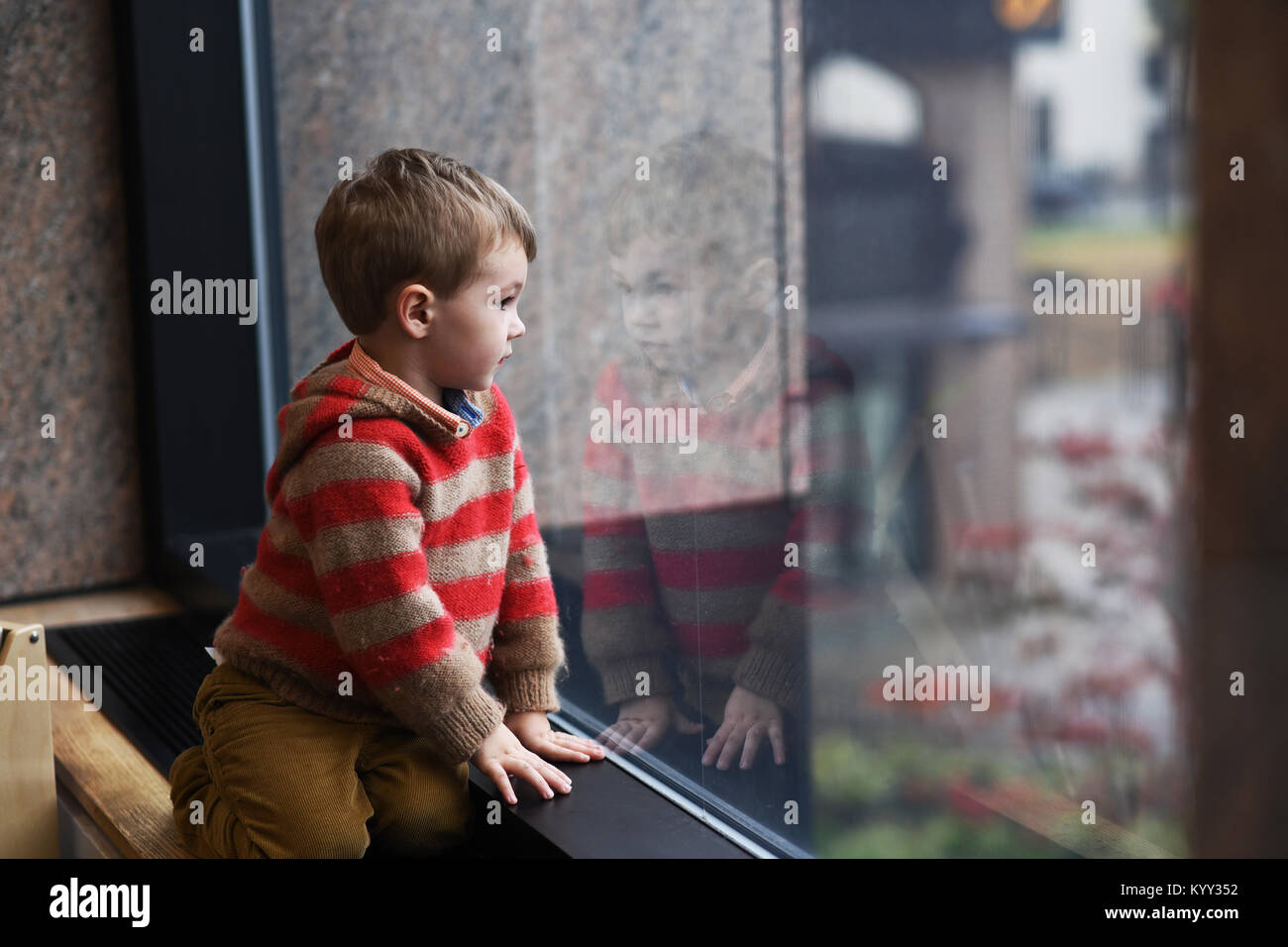 Boy looking through window while kneeling at home - Stock Image