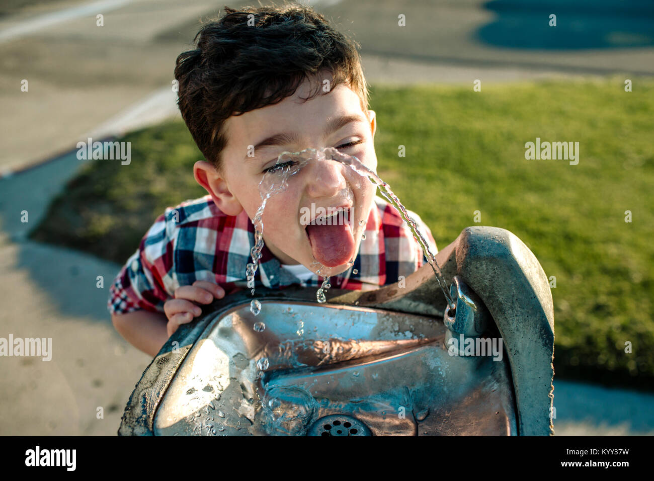 High angle view of playful boy drinking water from fountain - Stock Image