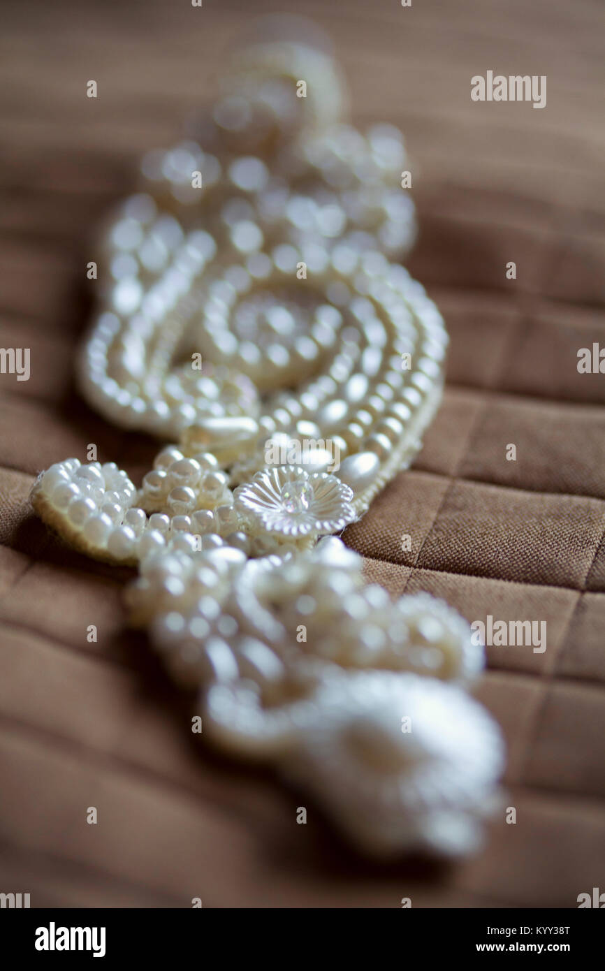 Close-up of wedding jewelry on textile - Stock Image