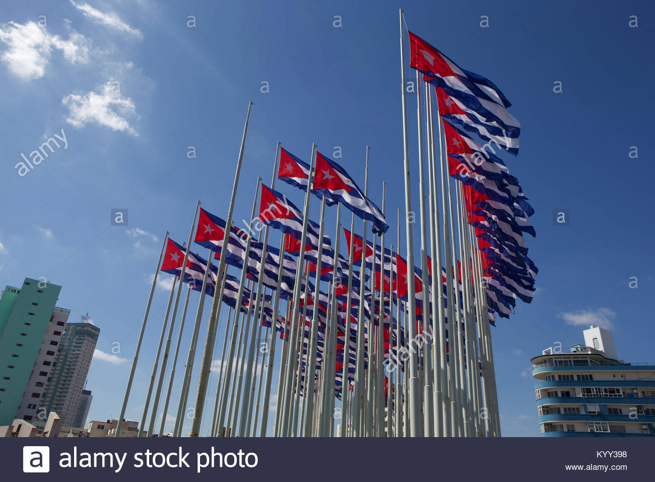 Low angle view of Cuban flags waving against blue sky in city - Stock Image