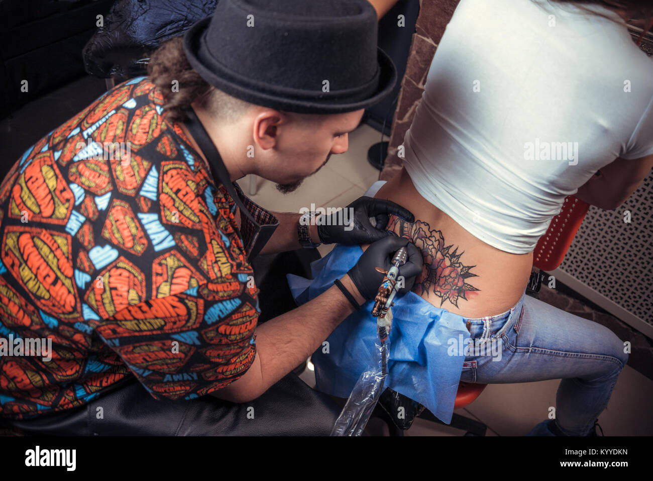 Master of the art of tattooing shows tattoo paint tatoo salon - Stock Image
