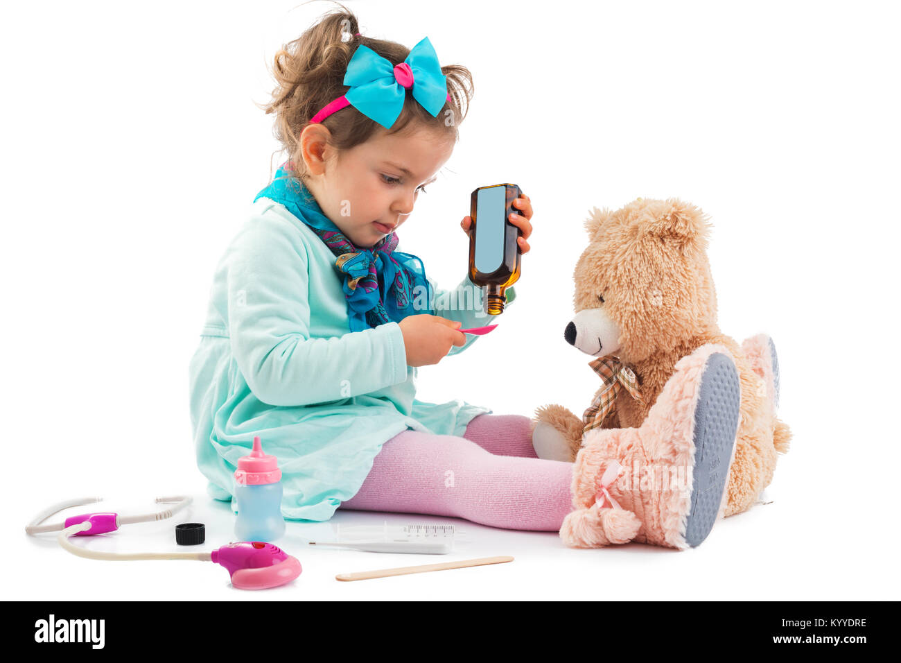 Cute kid girl playing doctor with plush toy at home. - Stock Image