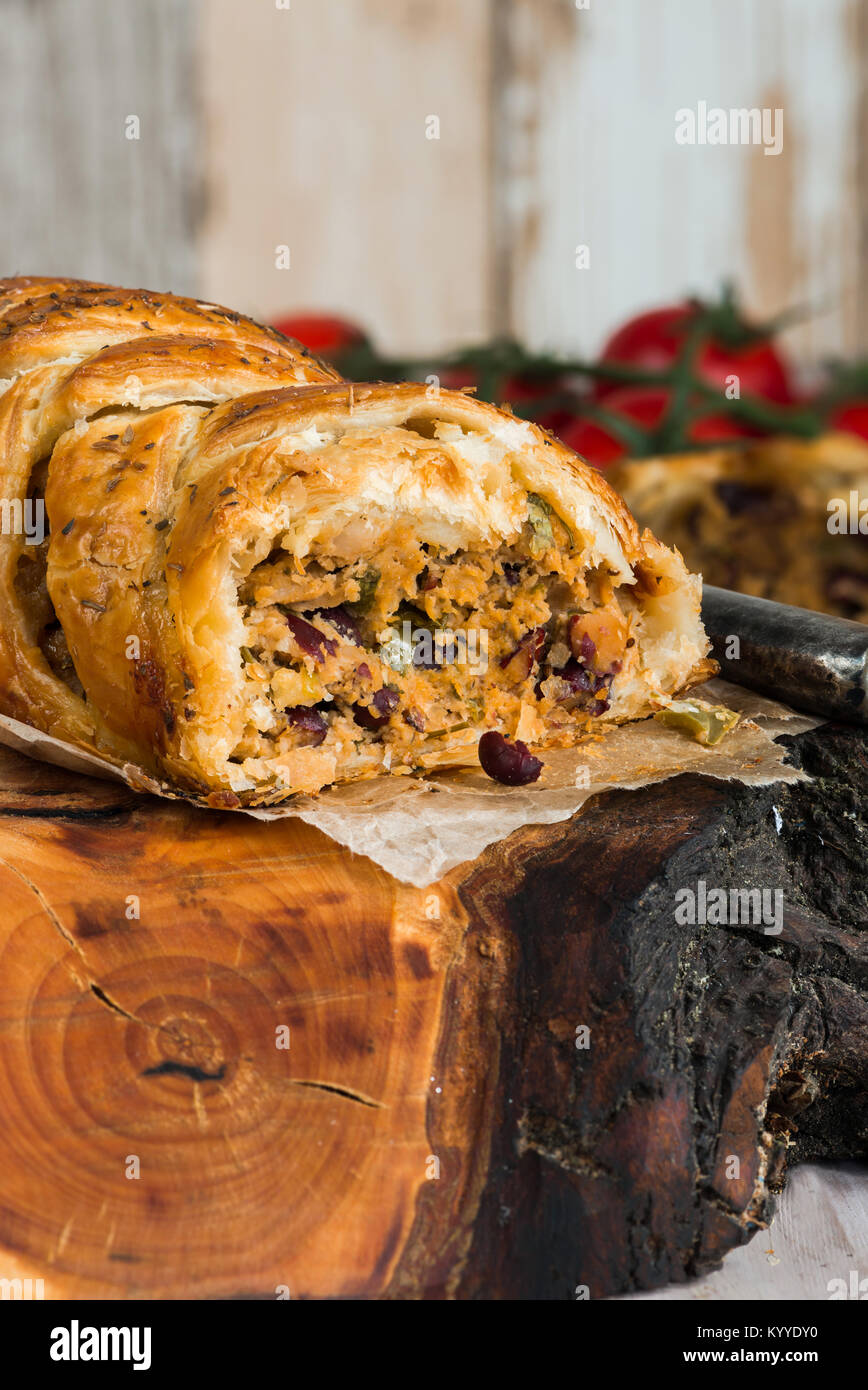 Pork roll - spicy sausage meat with chillies and beans in puff pastry on wooden table - Stock Image