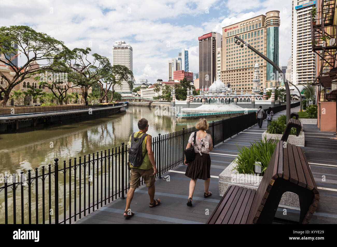 Kuala Lumpur, Malaysia - December 22, 2017: Tourists walk on the new promenade along the Klang river in front of - Stock Image