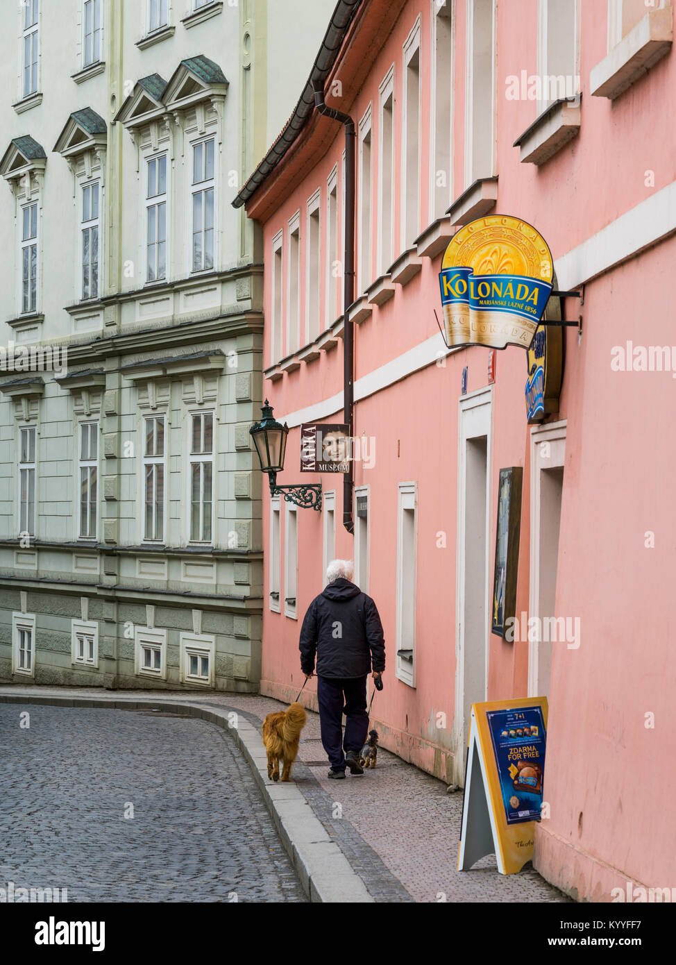 Man walking with two dogs in front of Kafka Museum, Prague, Czech Republic - Stock Image