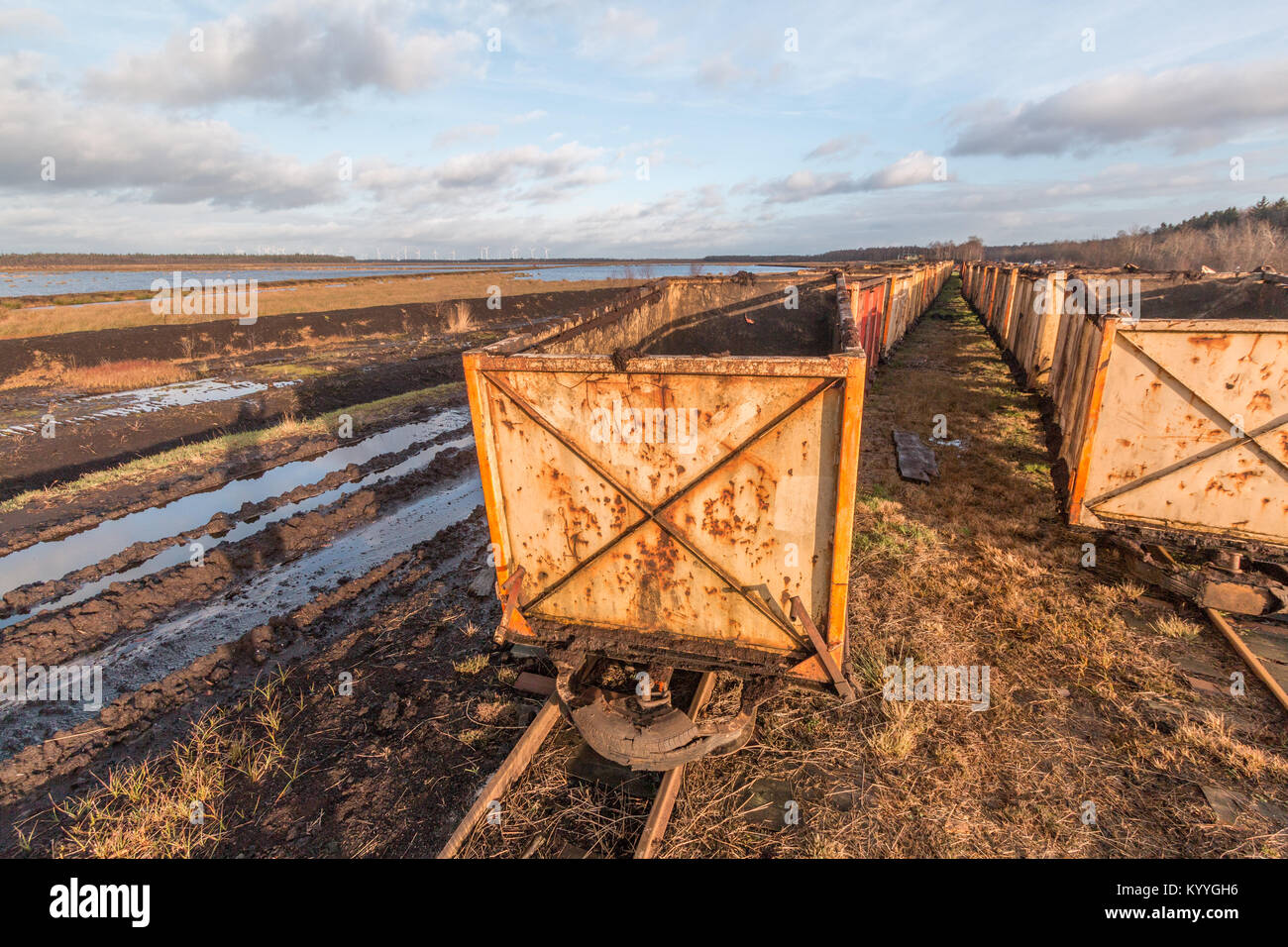 Peat mining area with old empty carts in the foreground - Stock Image