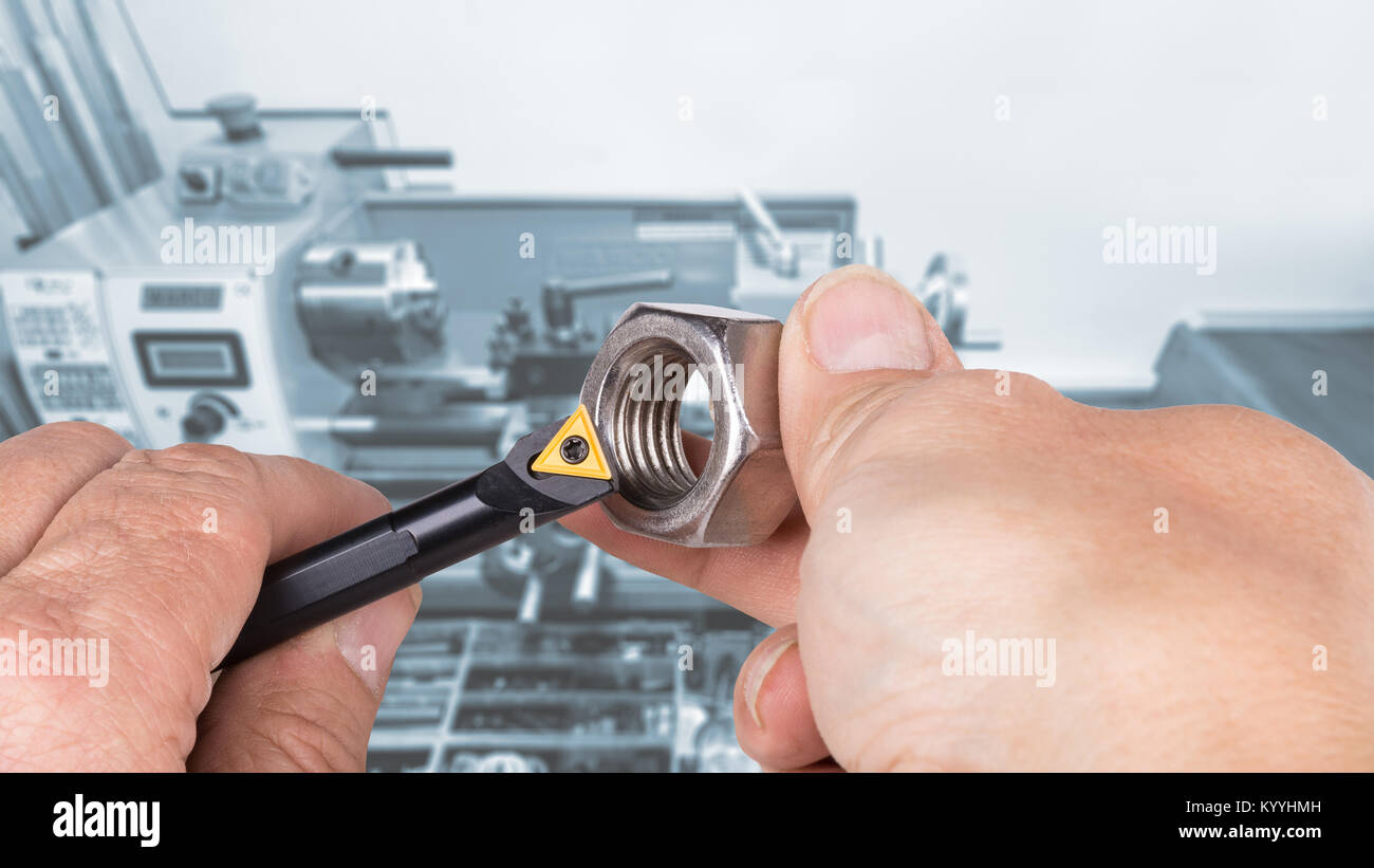 Lathe cutter for machining holes and metal hexagonal nut on blur background. Human hands and cutting tool. Concept - Stock Image