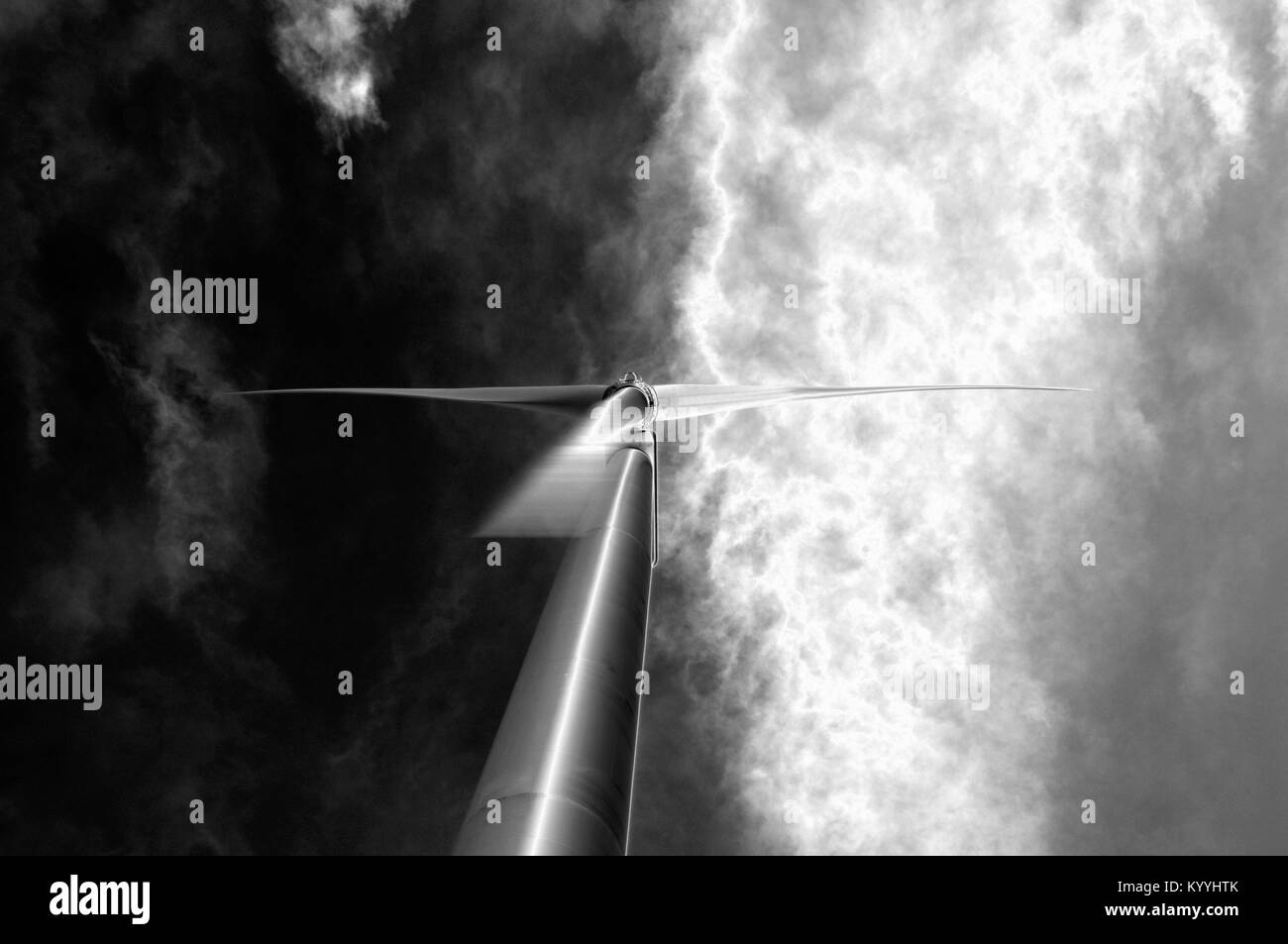 Blades of a wind turbine rotate as clouds pass overhead - Stock Image