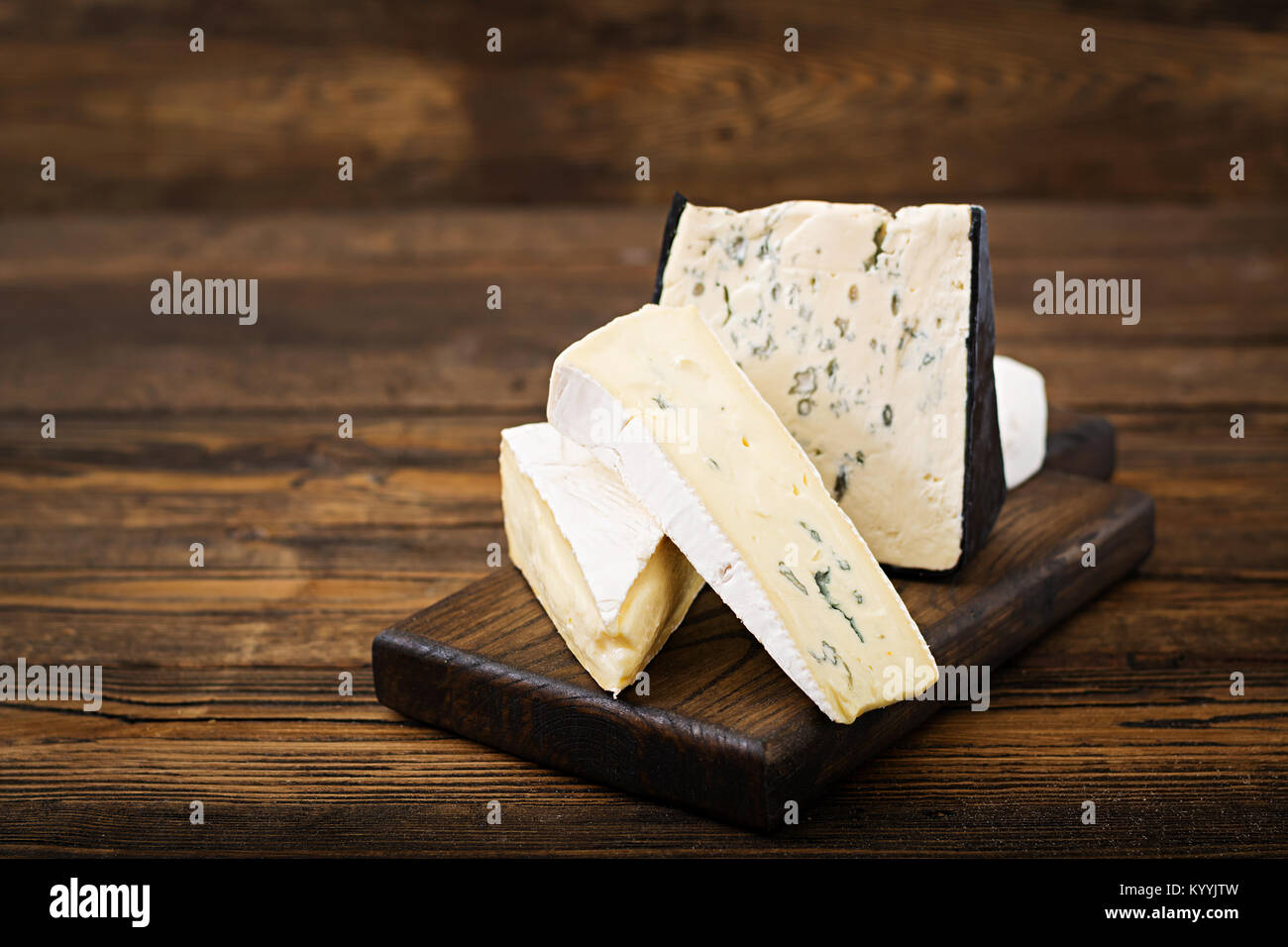 Assortment of cheeses. Camembert, dor blu, brie on a wooden background - Stock Image
