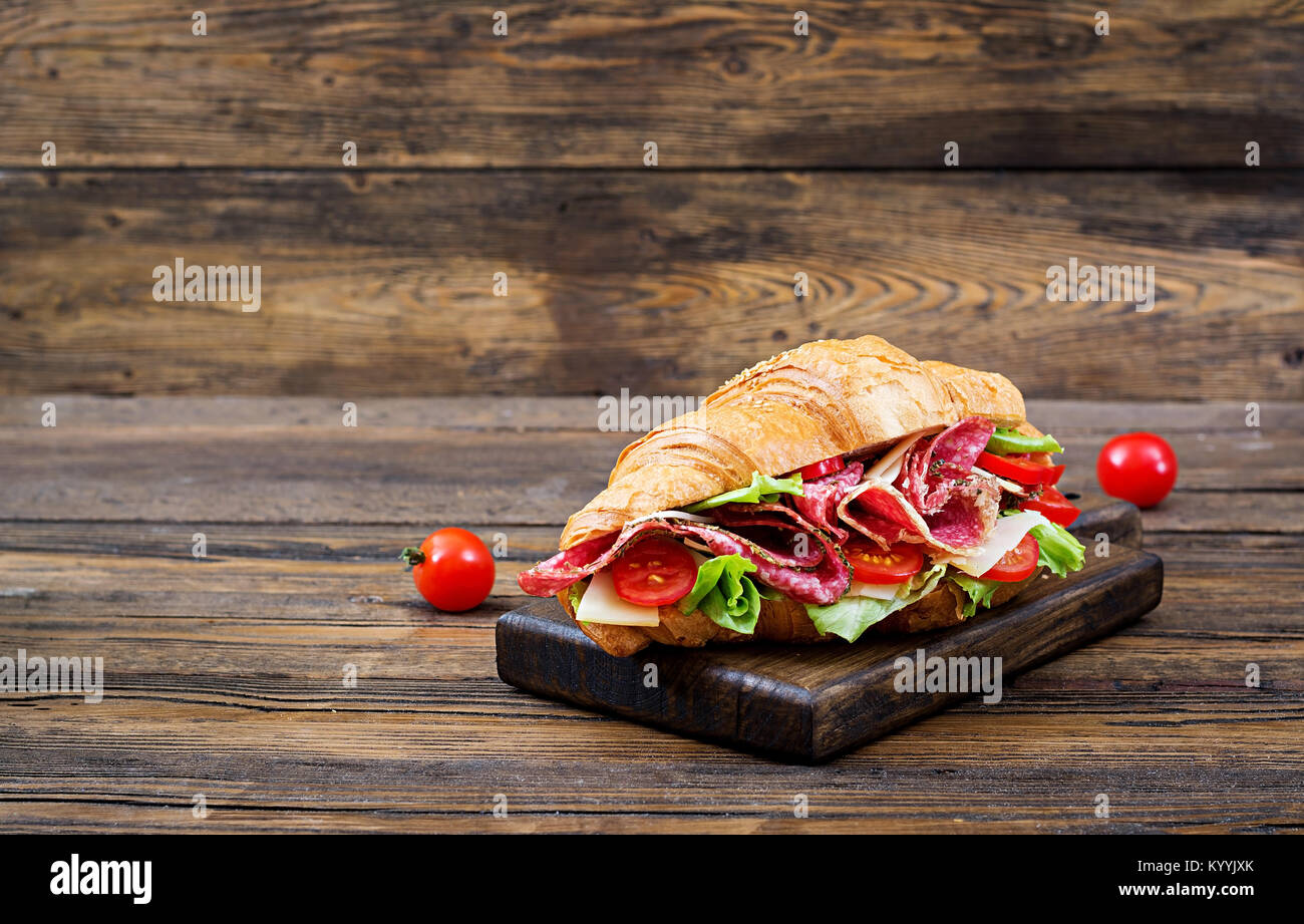 Tasty breakfast. Appetizing croissant with salami and, cheese and tomatoes - Stock Image