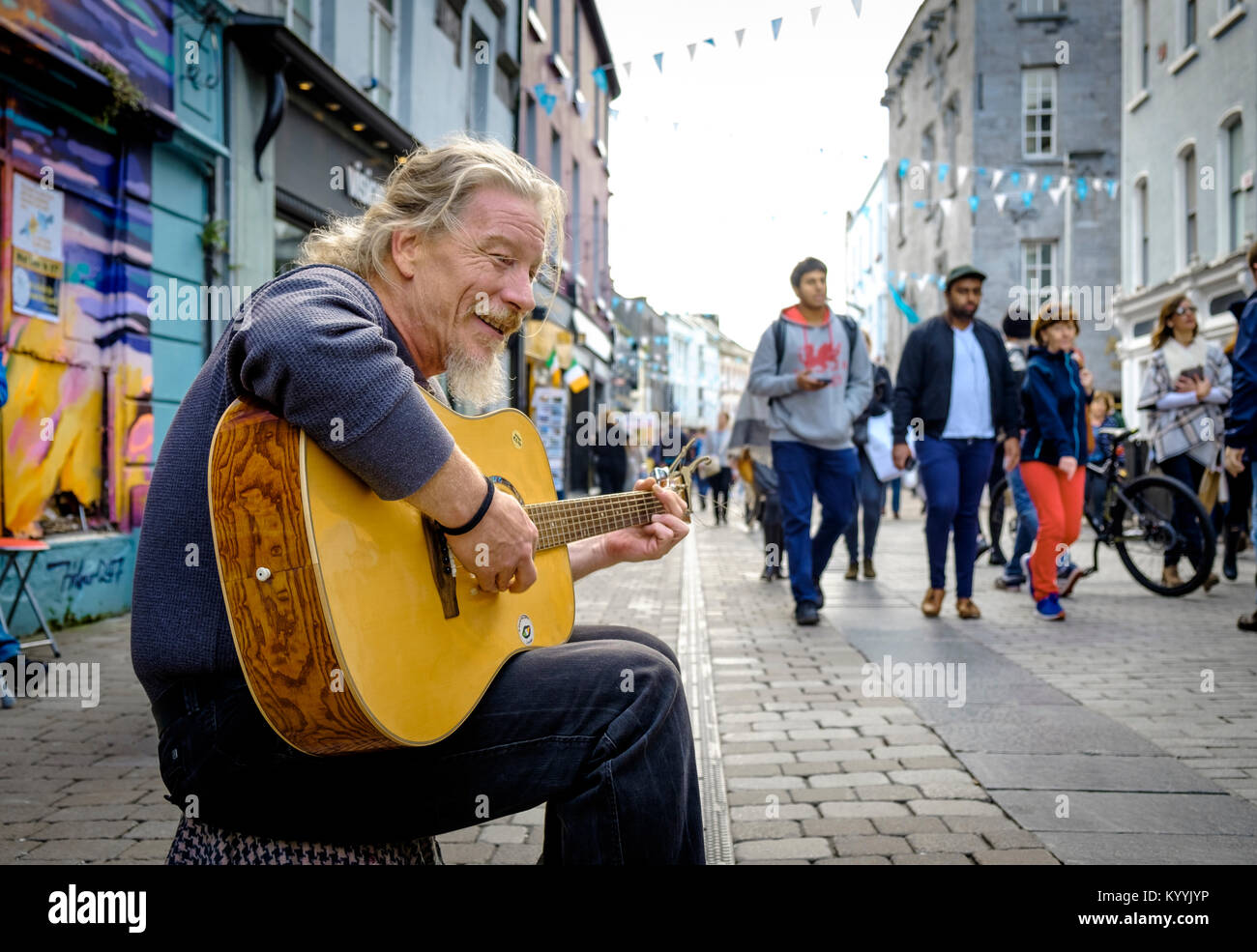 Busker busking on the High Street in the city centre of Galway, Ireland - Stock Image